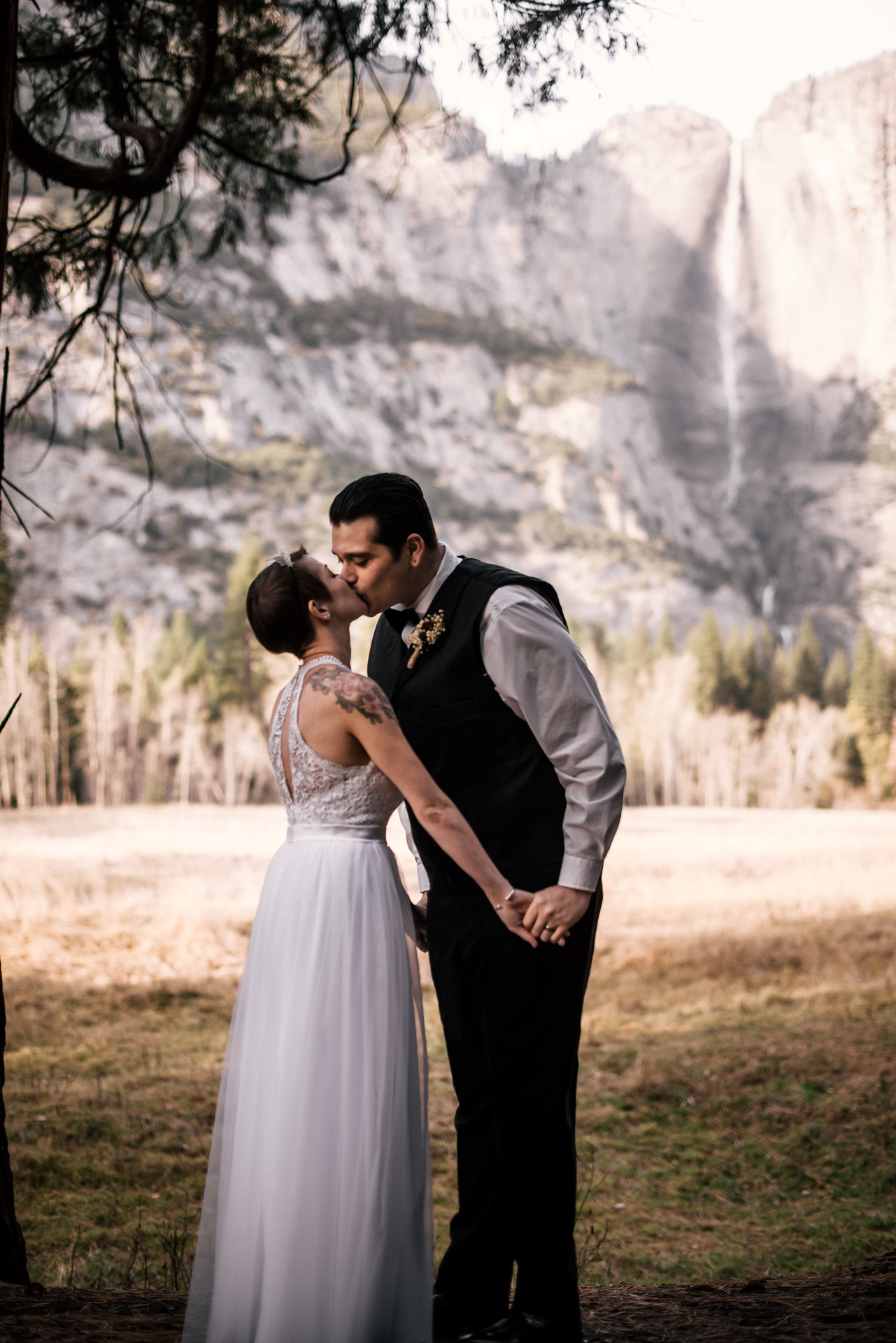 bride and groom share their first kiss with Yosemite falls in the background in yosemite national park California