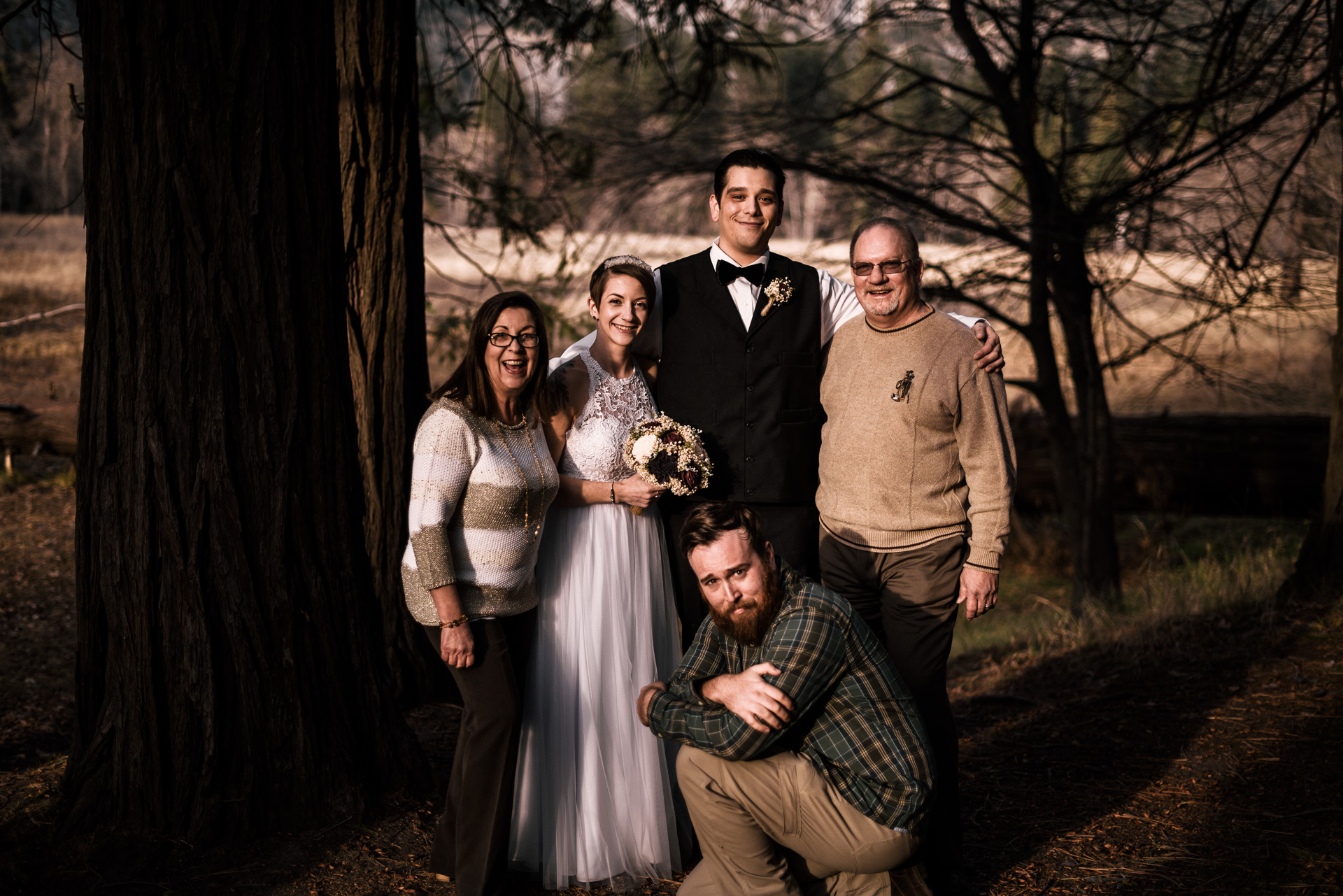 Norm Roberts from Fifth Photography poses with his happy wedding clients after their Yosemite elopement at swinging bridge