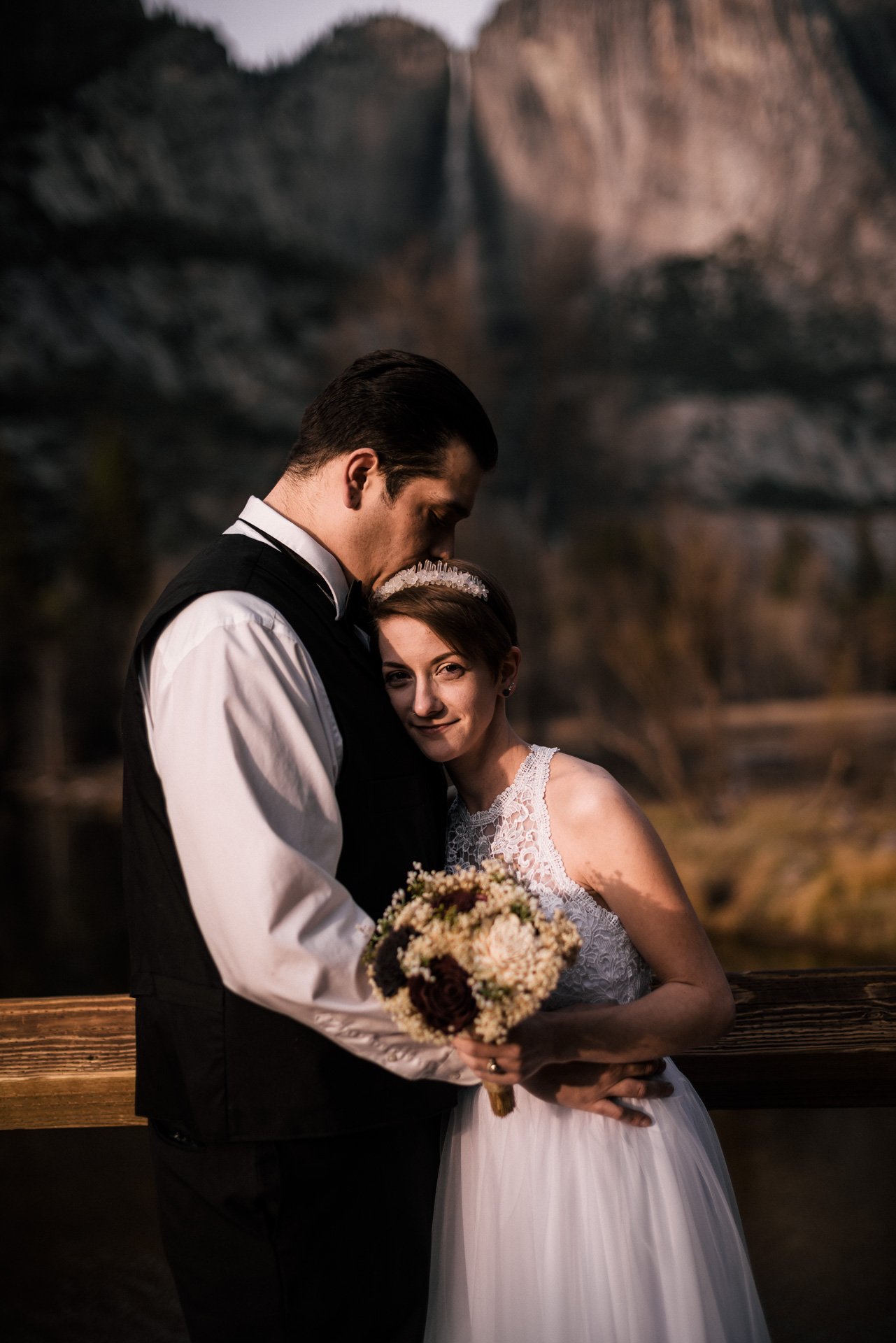 Bride and groom get lost in each others arms after their yosemite elopement at swinging bridge