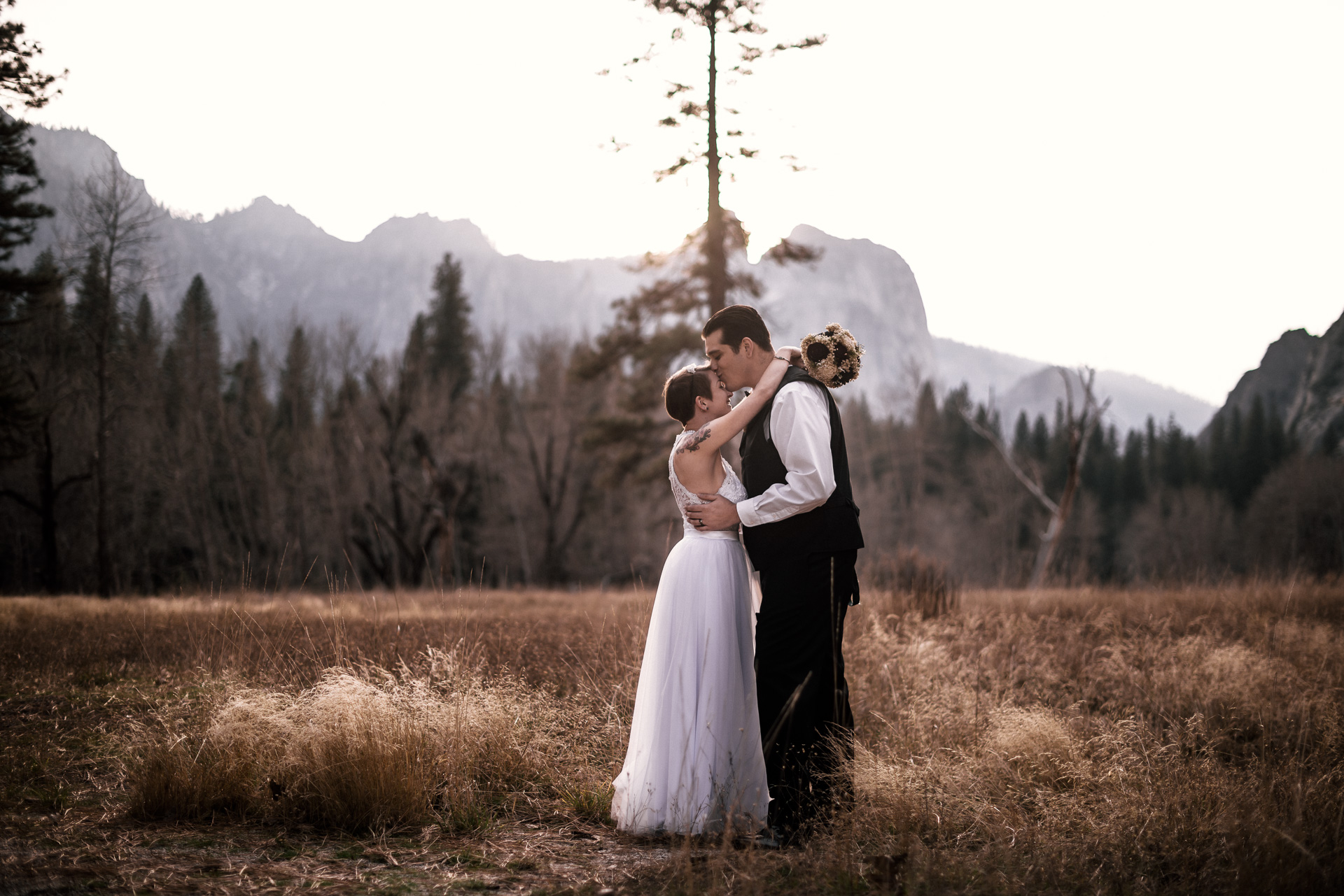 groom kisses brides forehead in a yosemite meadow at sunset