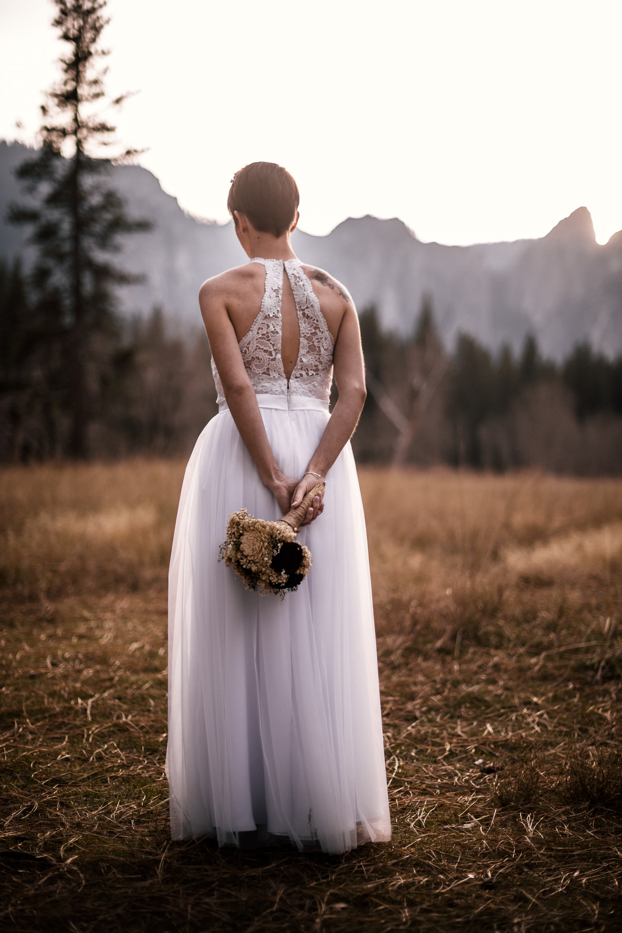 Bride poses with bouquet showing the detials of her wedding dress in yosemite national park