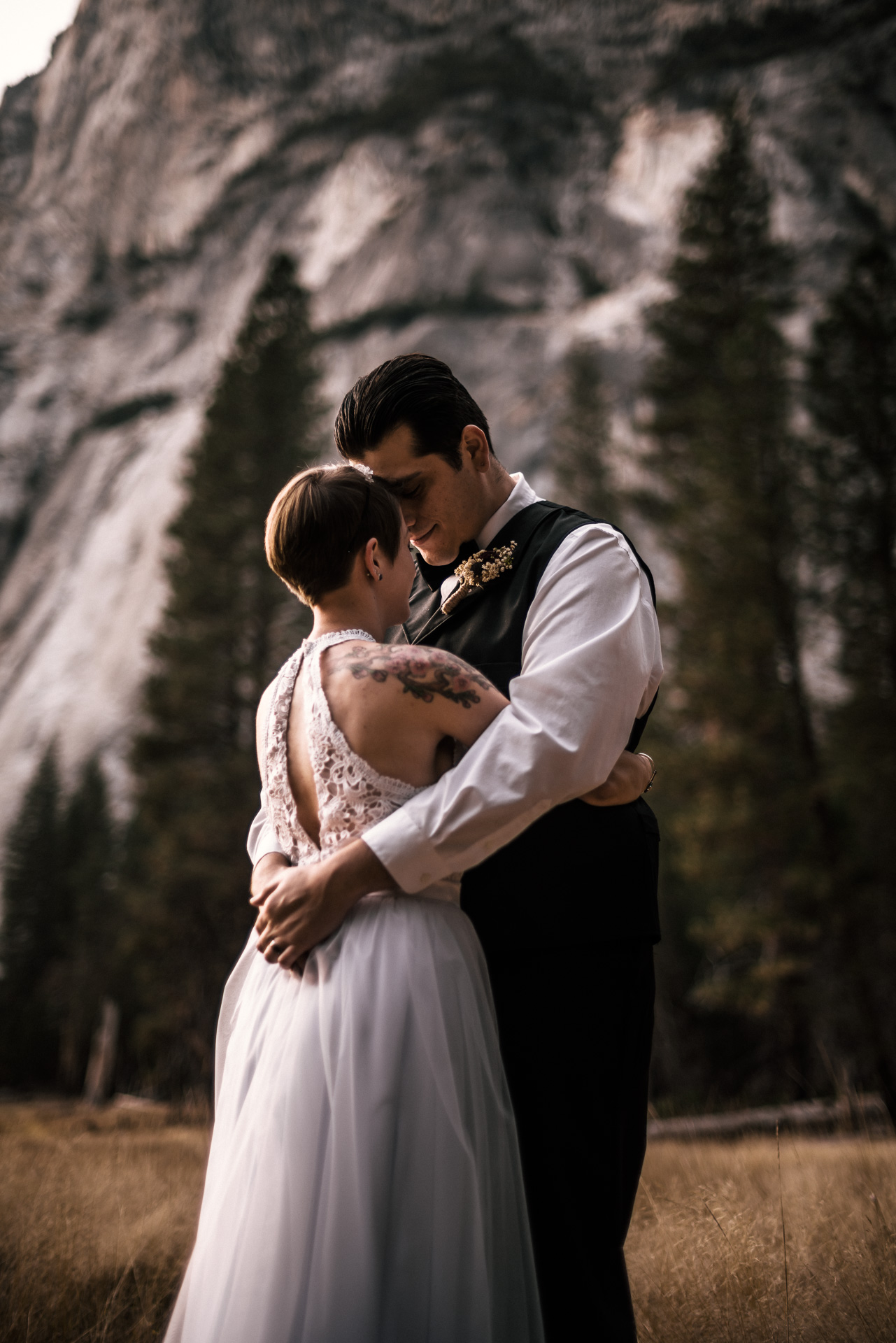 couple get lost in each others arms at swinging bridge in yosemite national park