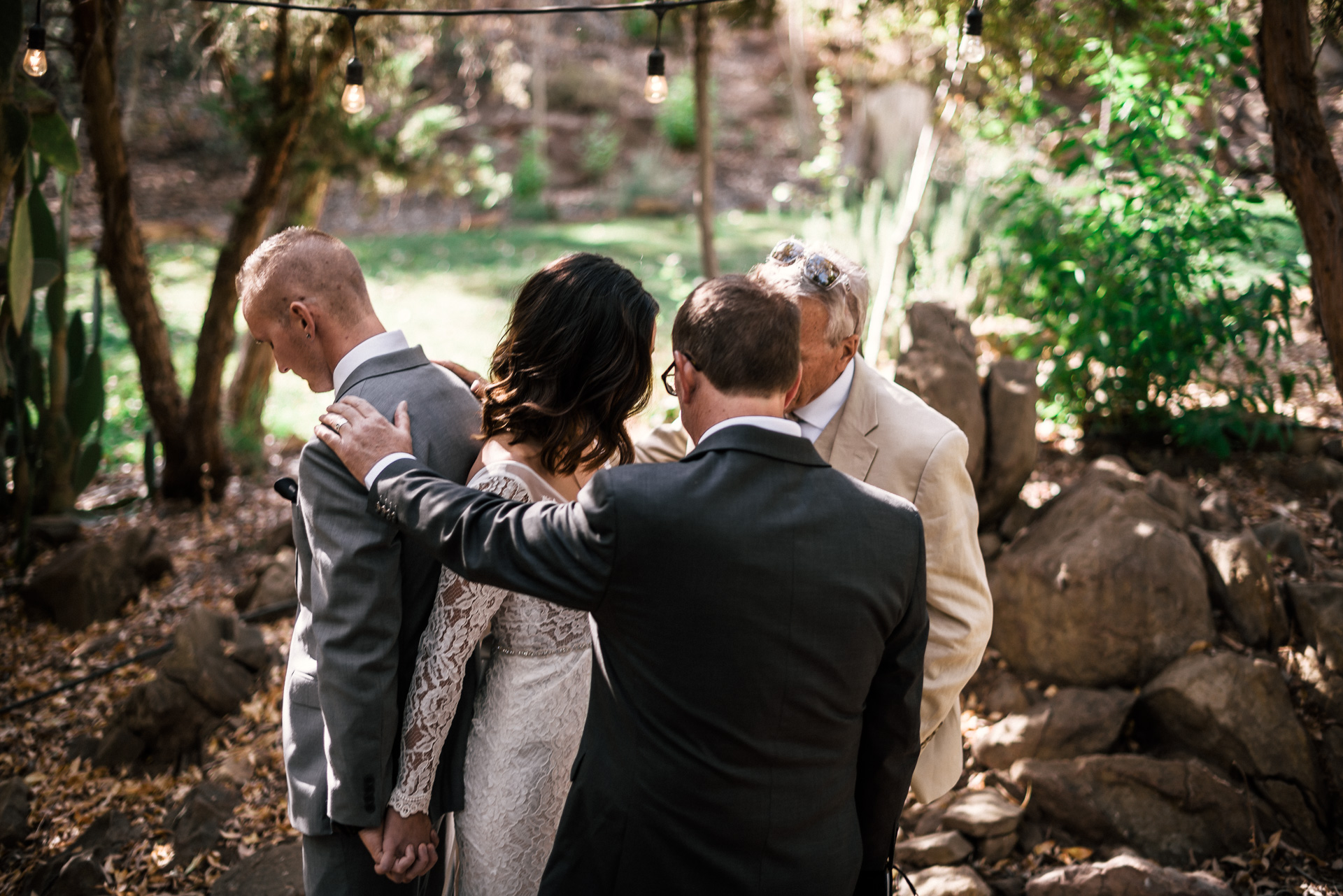 Bride and grooms fathers pray over them at rustic Pymm ranch wedding venue in Winchester california