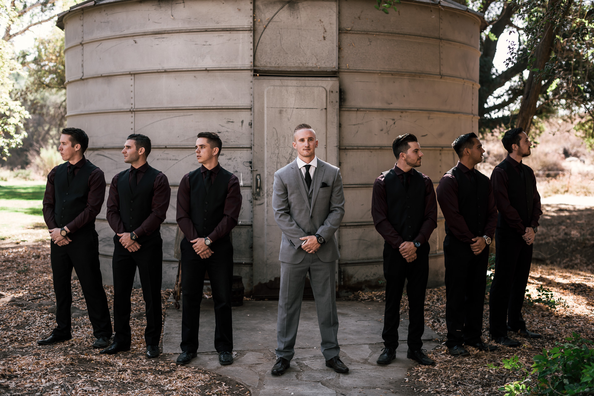 groom poses with groomsmen at rustic pymm ranch wedding venue in winchester california