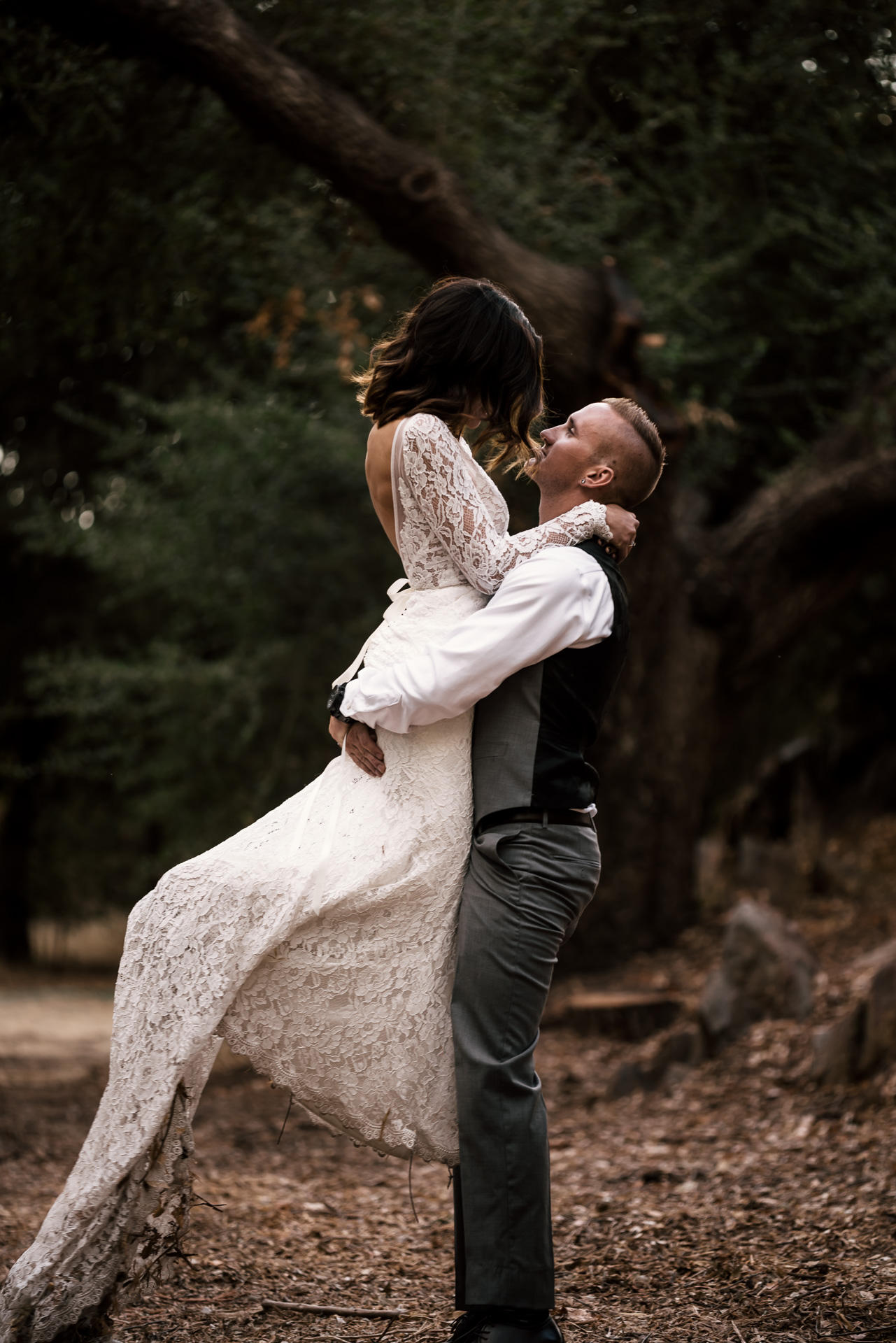 groom lifts bride at rustic pymm ranch wedding venue in winchester california