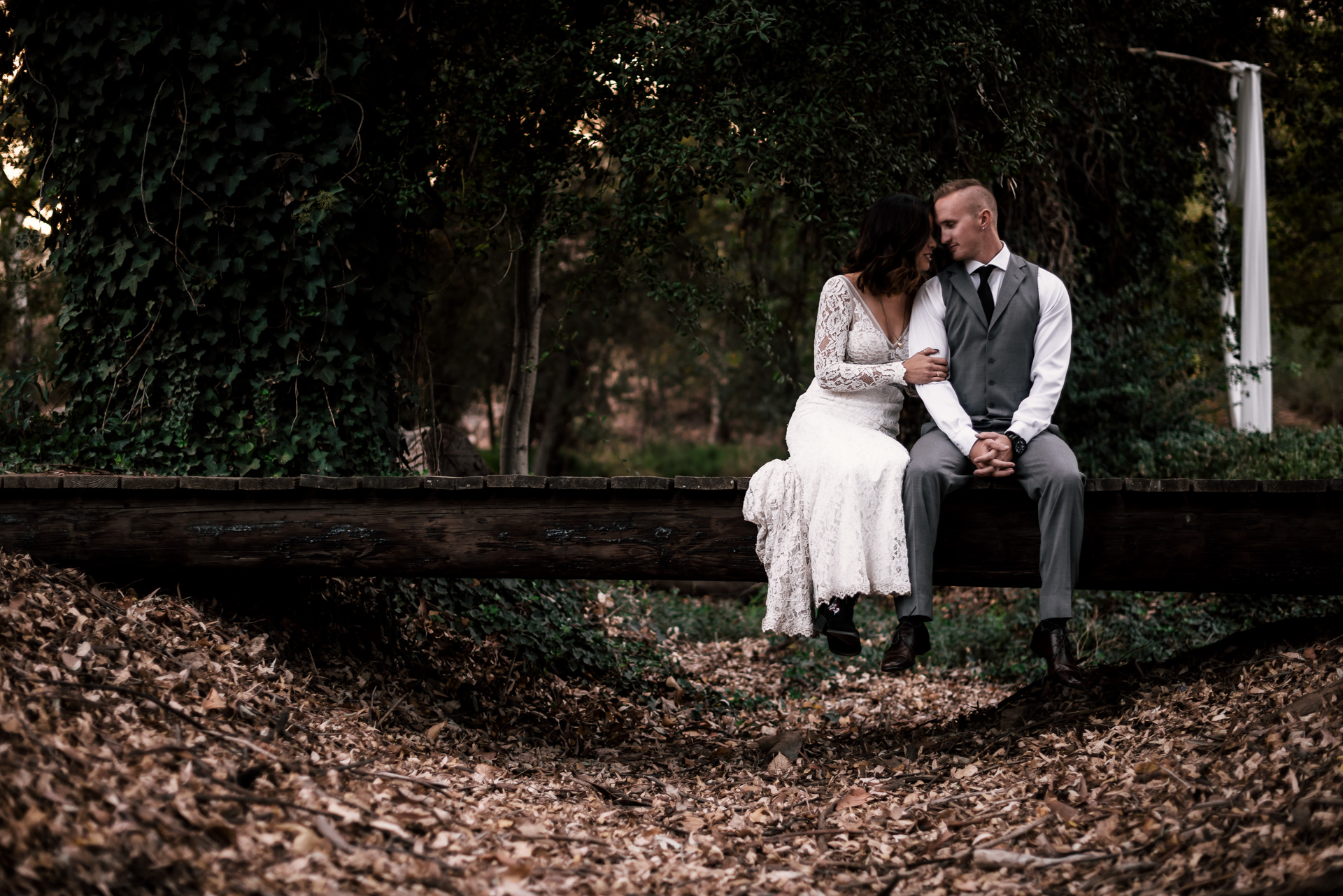 bride and groom sit on rustic bridge at rustic pymm ranch wedding venue in winchester california