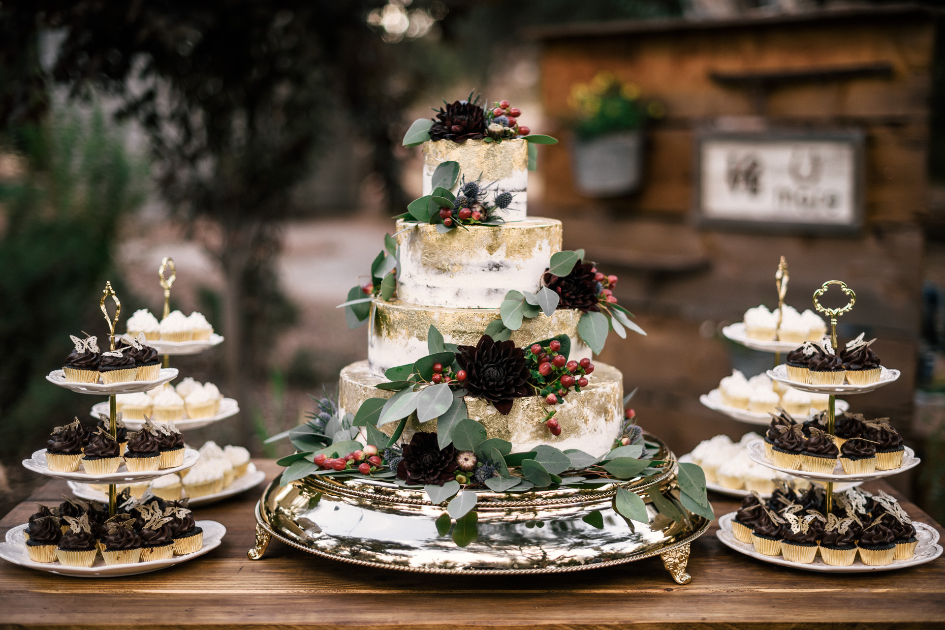 wedding cake with black flowers, gold leaf and eucalyptus details at rustic pymm ranch wedding venue in winchester california