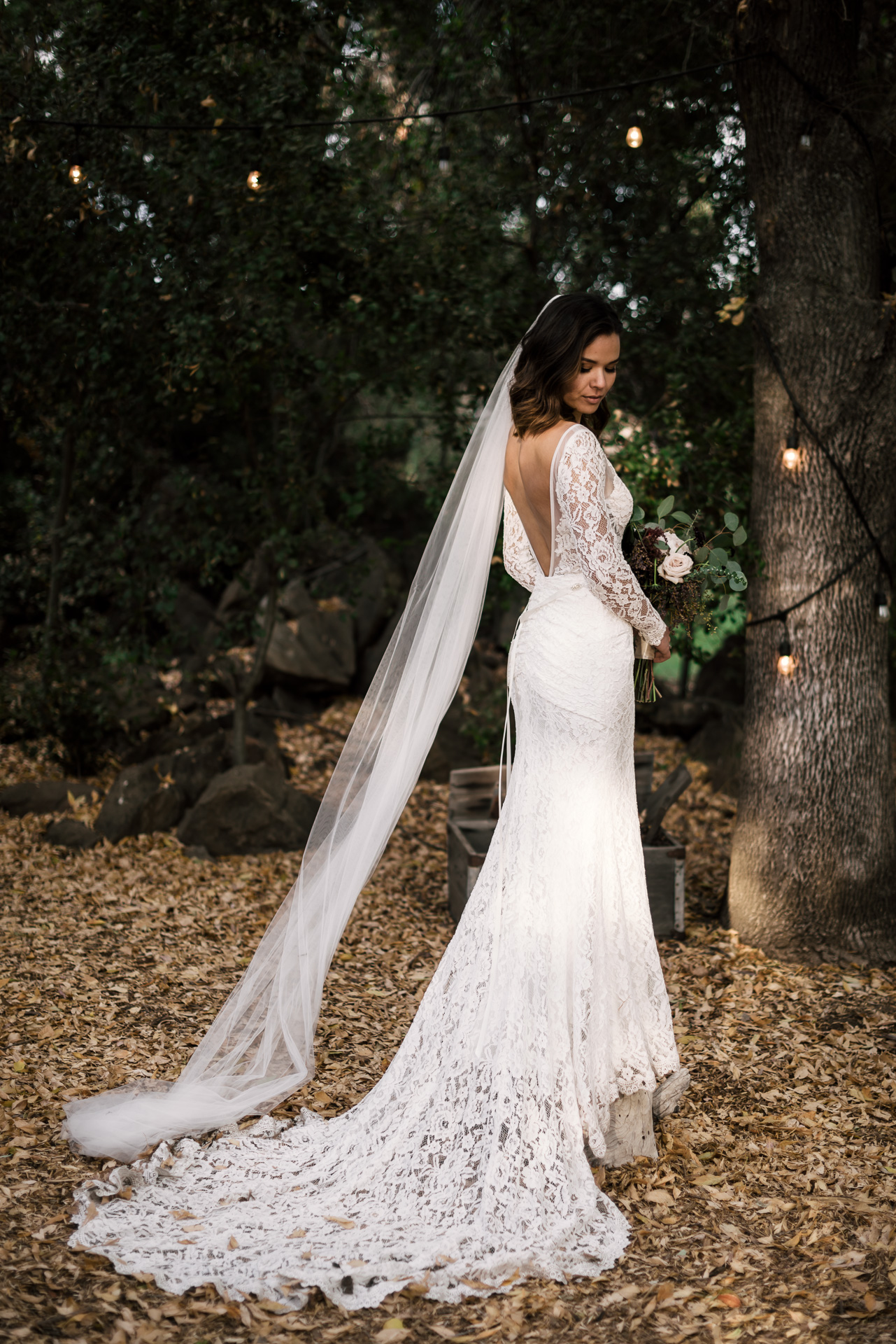 Bride shows off her lace dress at rustic pymm ranch wedding venue in Winchester california