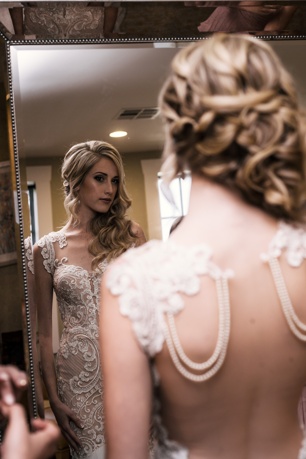 bride looks at her stunning wedding dress in the mirror at the Twin Oaks Golf Course in San Marcos, San Diegos premier wedding venue