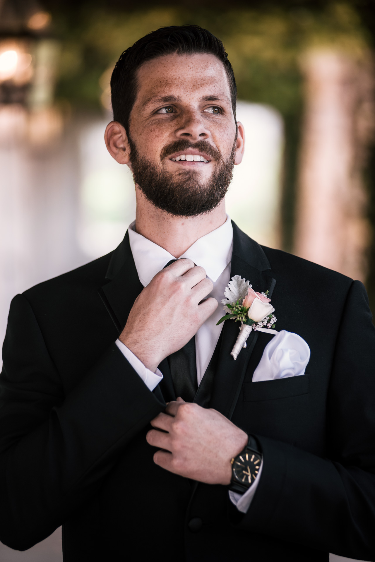 Groom fixes his tie while he waits to see his bride at the first look at the Twin Oaks Golf Course in San Marcos, San Diegos premier wedding venue