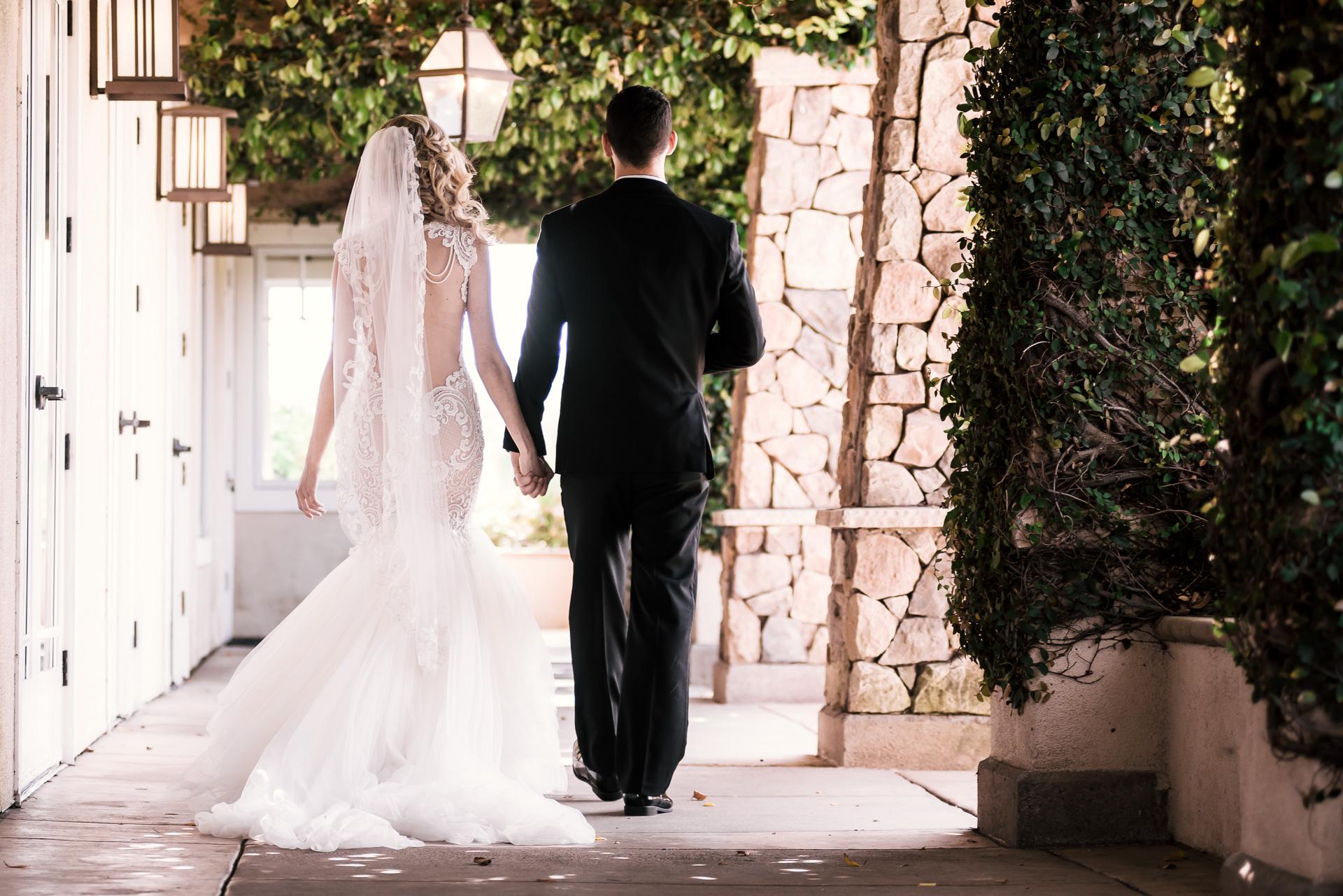 bride and groom take a walk beneath ivy at the Twin Oaks Golf Course in San Marcos, San Diegos premier wedding venue