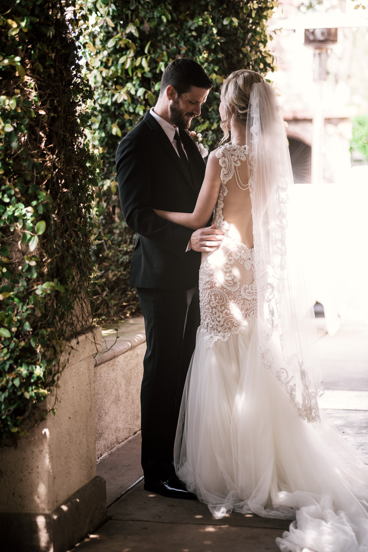 groom looks over his beautiful brides wedding dress at the Twin Oaks Golf Course in San Marcos, San Diegos premier wedding venue