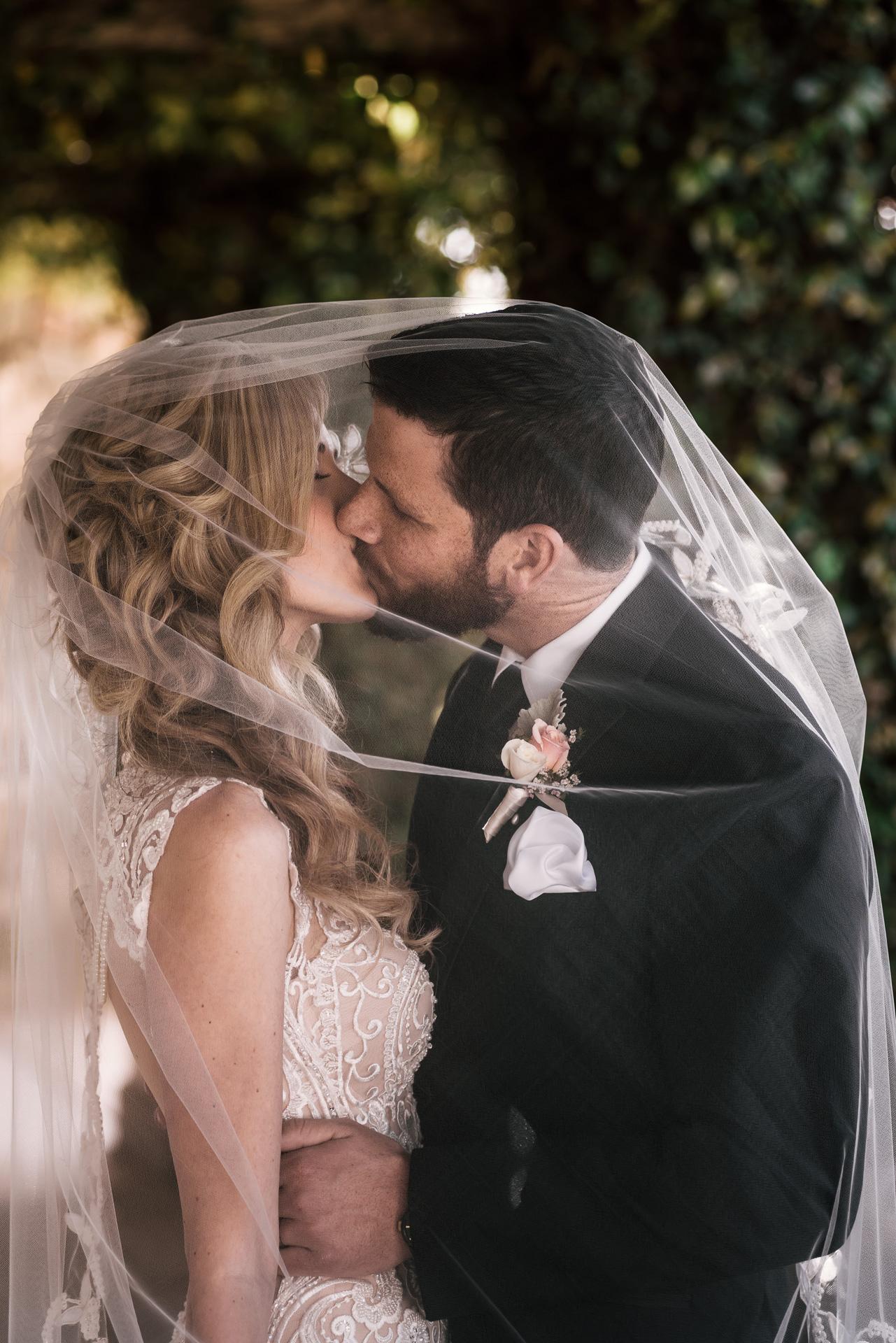 bride and groom kiss under their wedding veil at the Twin Oaks Golf Course in San Marcos, San Diegos premier wedding venue