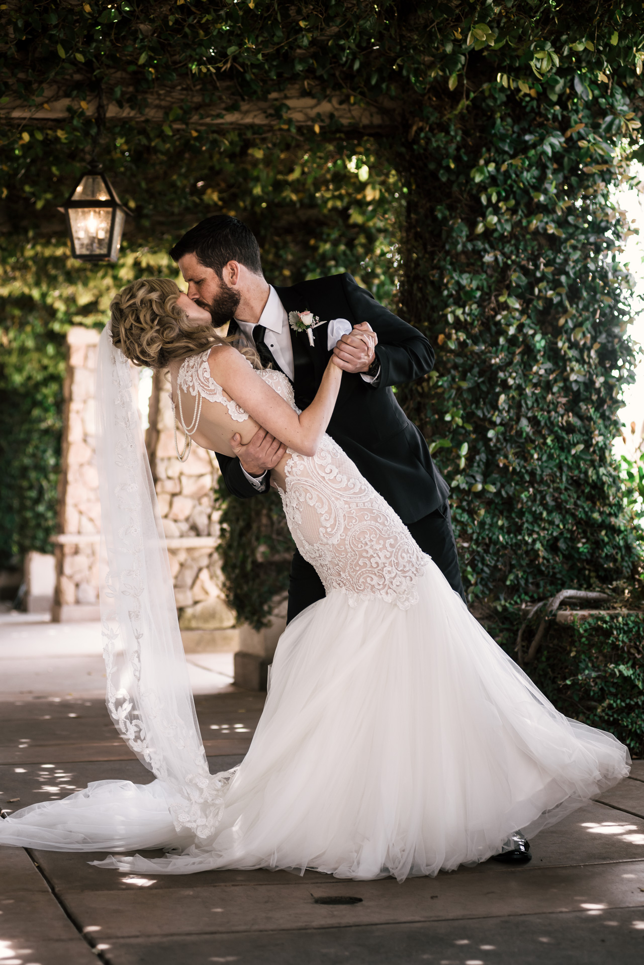 groom kiss his bride as he romanticaly dips her at the Twin Oaks Golf Course in San Marcos, San Diegos premier wedding venue