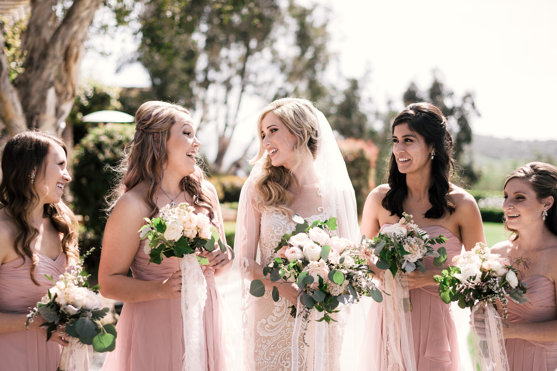 bride and her bridesmaids share a laugh at the Twin Oaks Golf Course in San Marcos, San Diegos premier wedding venue
