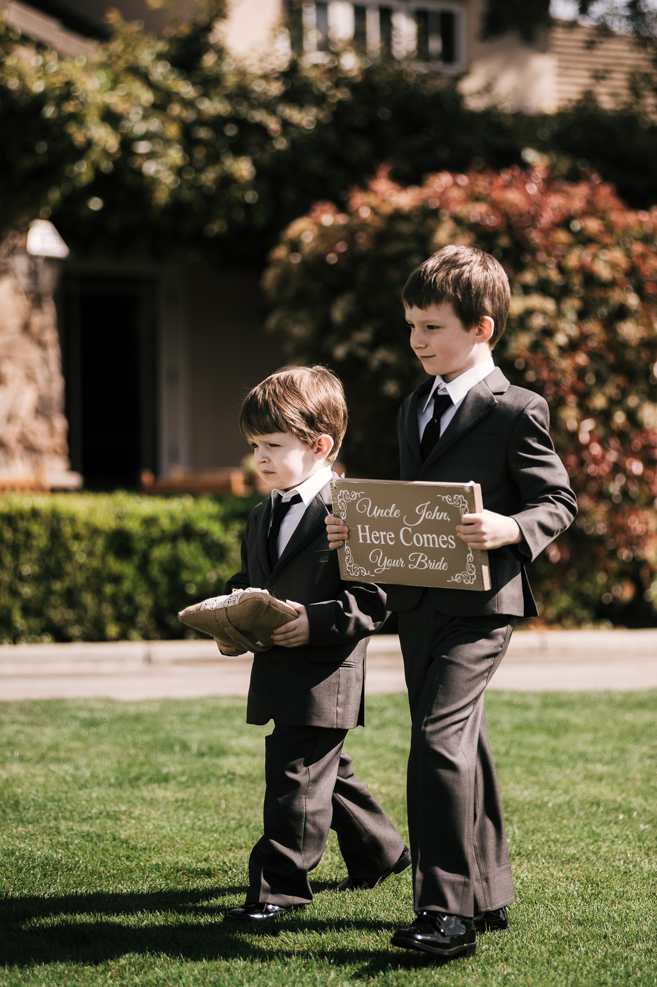 ring bearers walk down the aisle announcing the bride at the Twin Oaks Golf Course in San Marcos, San Diegos premier wedding venue