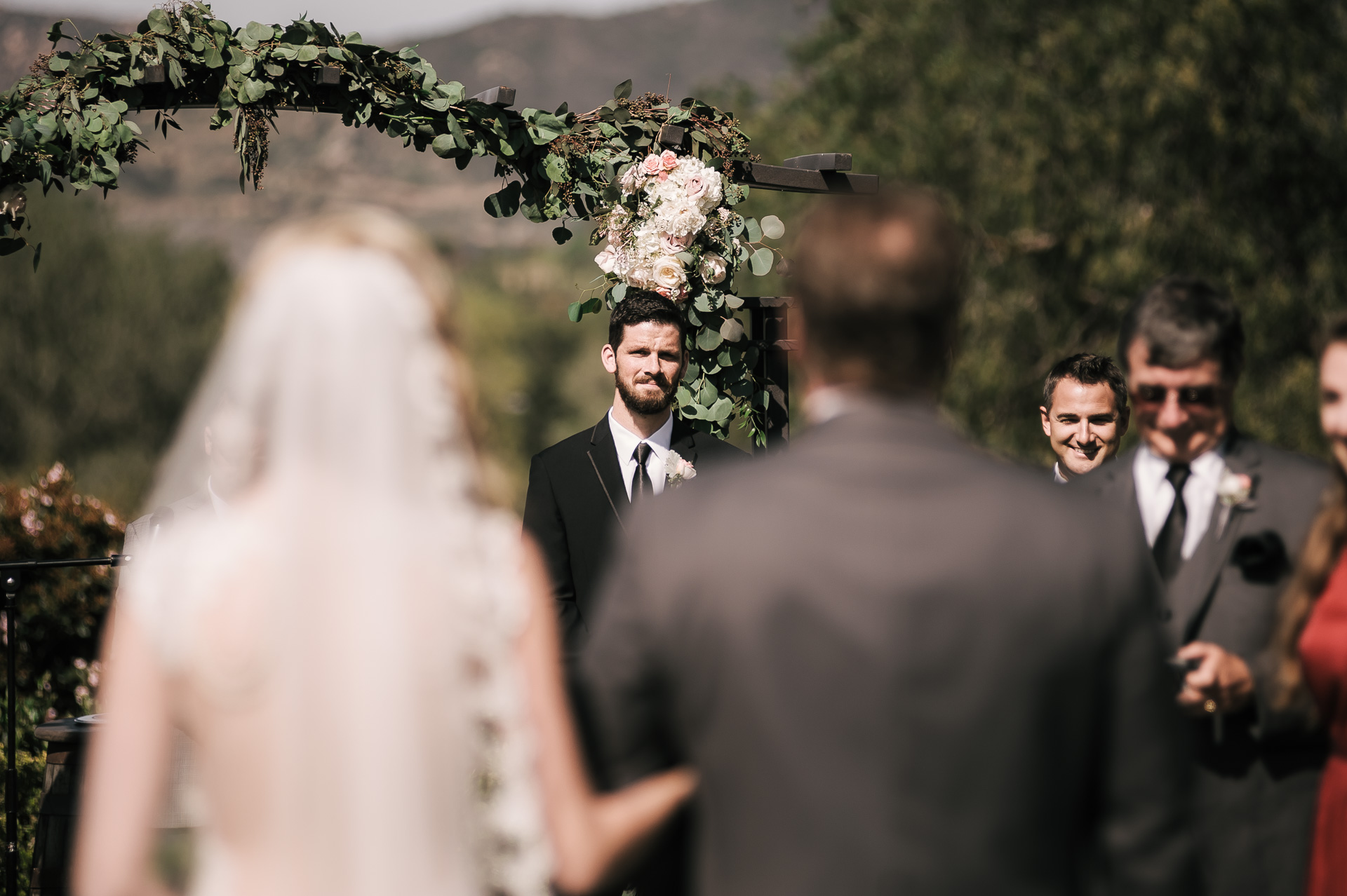 groom sees his bride for the first time coming down the aisle at the Twin Oaks Golf Course in San Marcos, San Diegos premier wedding venue