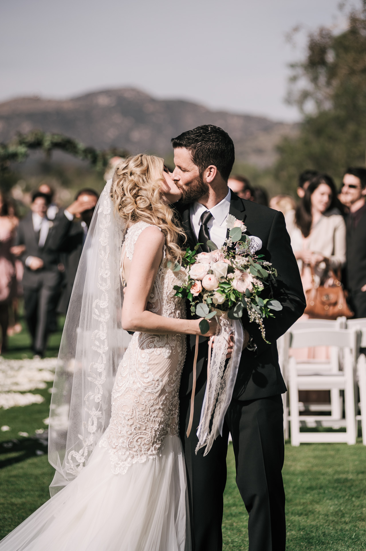 bride and groom share anotehr kiss before they make their exit at the Twin Oaks Golf Course in San Marcos, San Diegos premier wedding venue