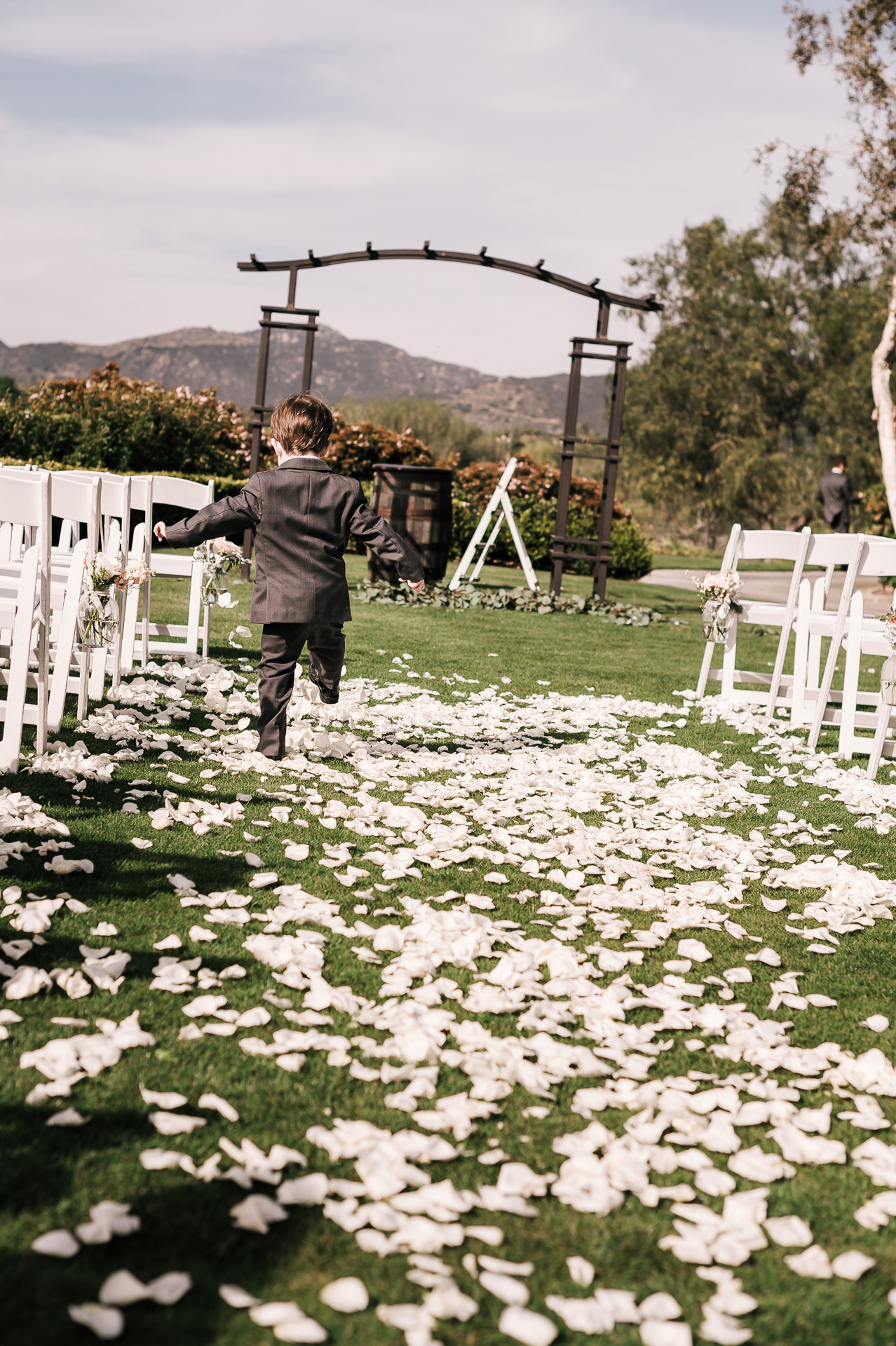 ring bearer plays in the flower petals after wedding ceremony at the Twin Oaks Golf Course in San Marcos, San Diegos premier wedding venue