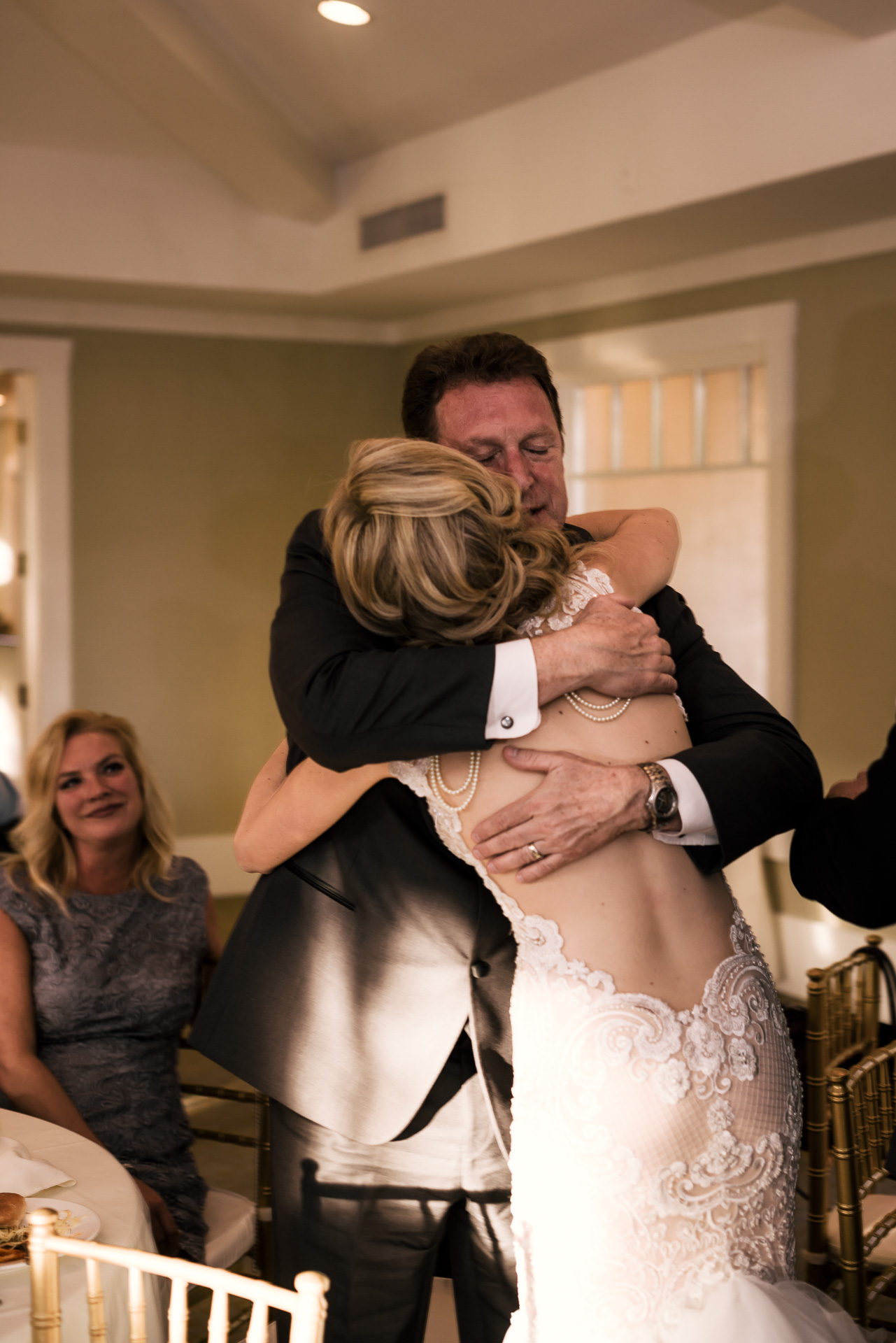 bride gives her father a hug at the Twin Oaks Golf Course in San Marcos, San Diegos premier wedding venue