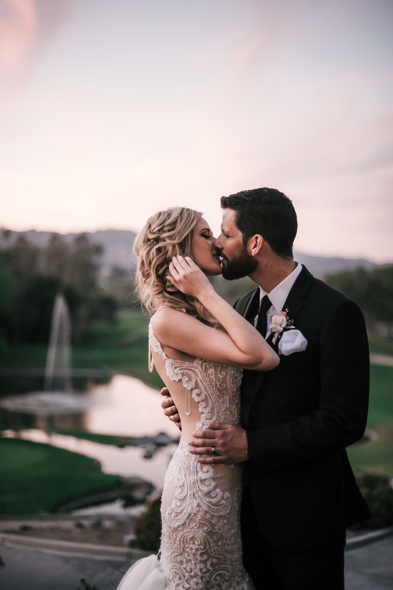 groom romantically kisses bride at sunset at the Twin Oaks Golf Course in San Marcos, San Diegos premier wedding venue