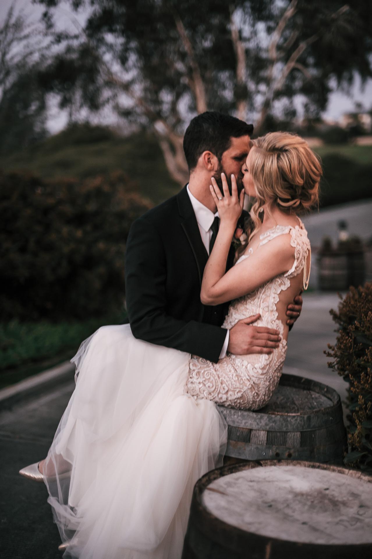 groom kiss bride sitting on a rustic barrel at the Twin Oaks Golf Course in San Marcos, San Diegos premier wedding venue