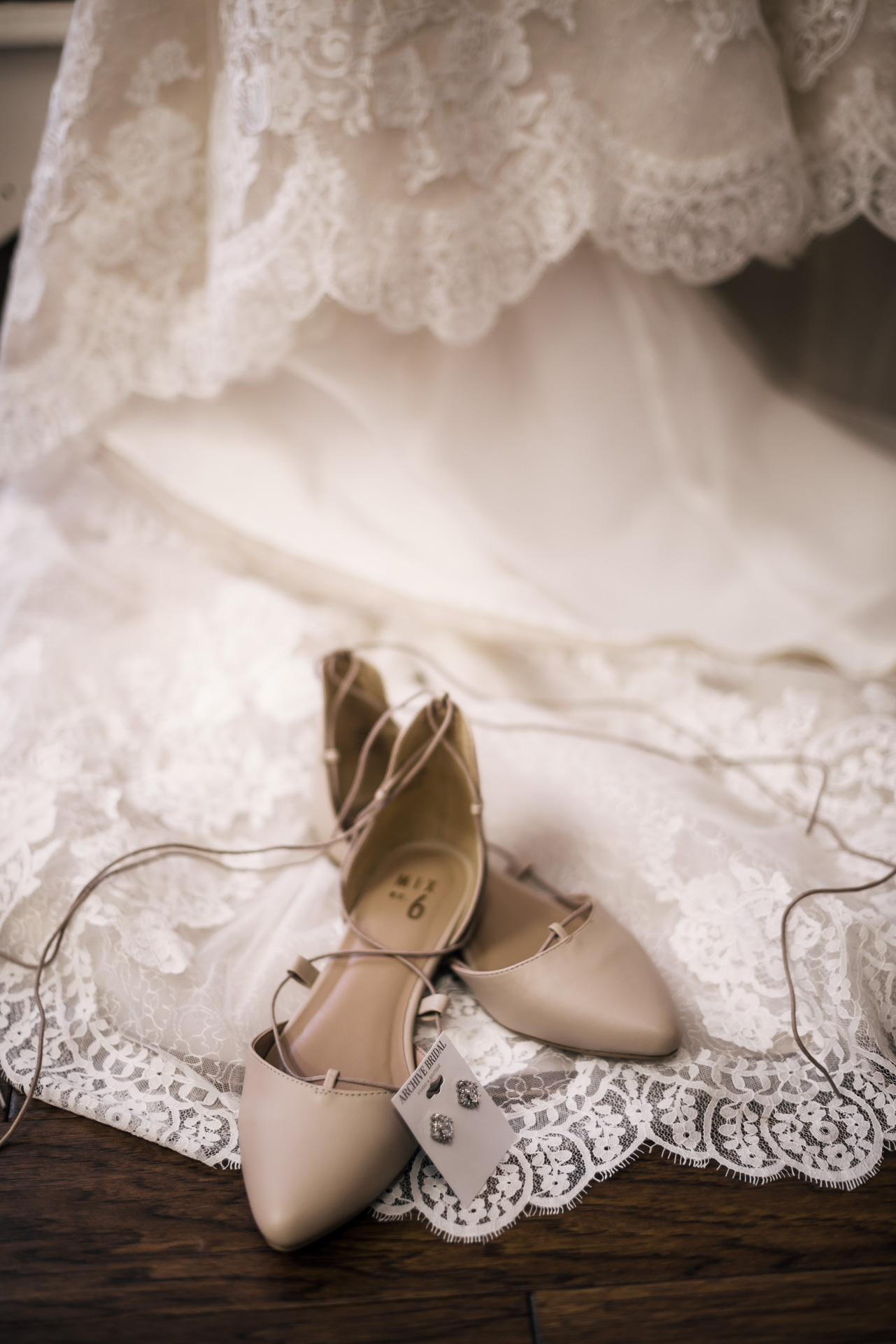 wedding shoes and jewlery displayed in front of brides dress at the secret garden located at the Historic Parish ranch in Oak Glen California