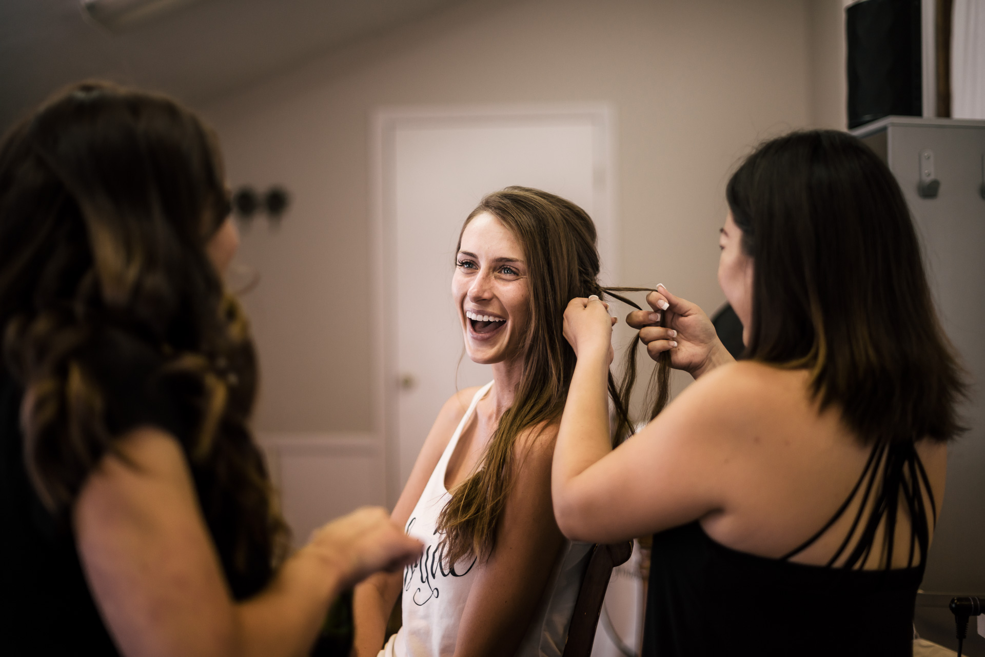 brides alughs with her bridesmaids as they do her hair at the secret garden located at the Historic Parish ranch in Oak Glen California