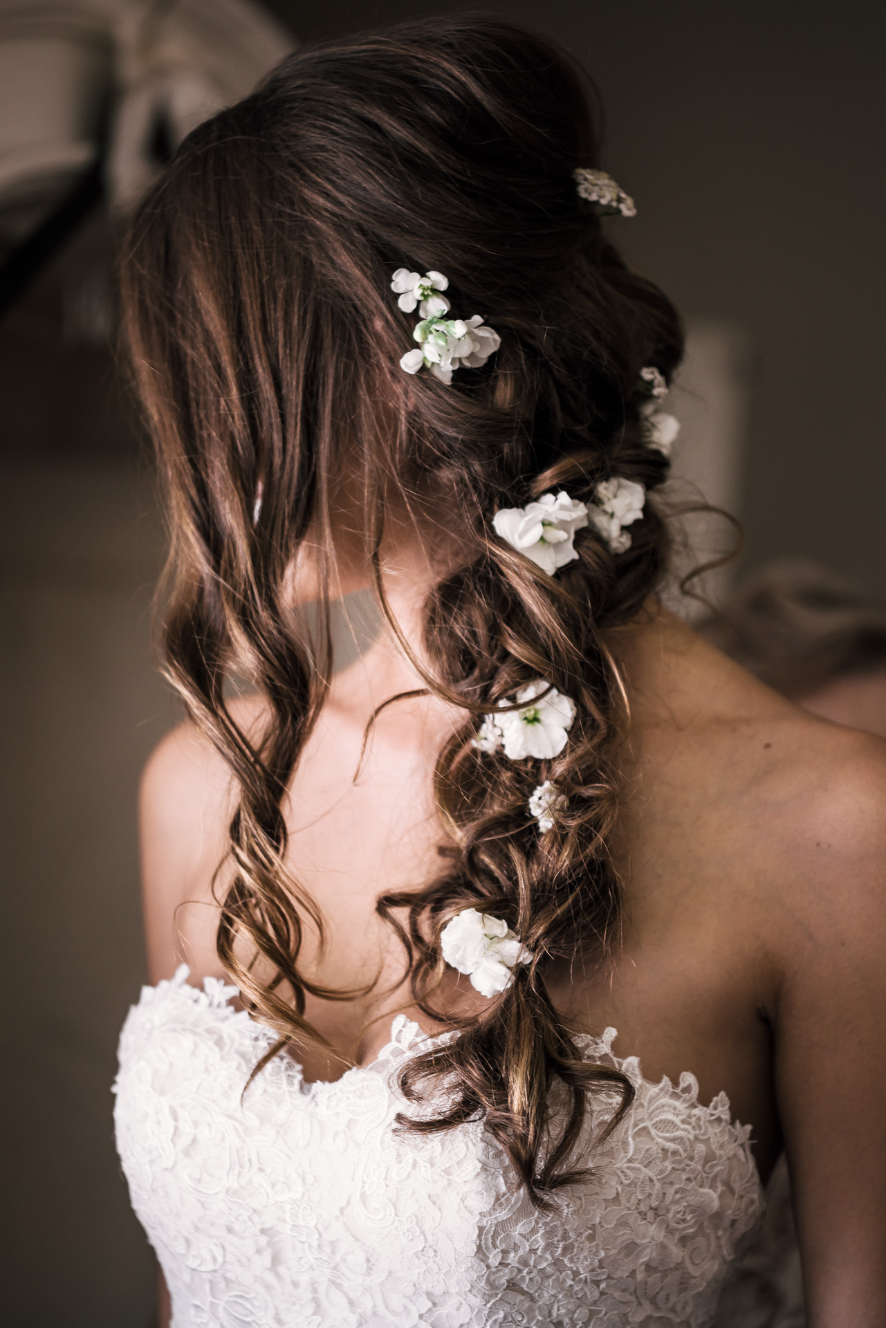 Bride in her wedding dress has flowers in her hair at the secret garden located at the Historic Parish ranch in Oak Glen California