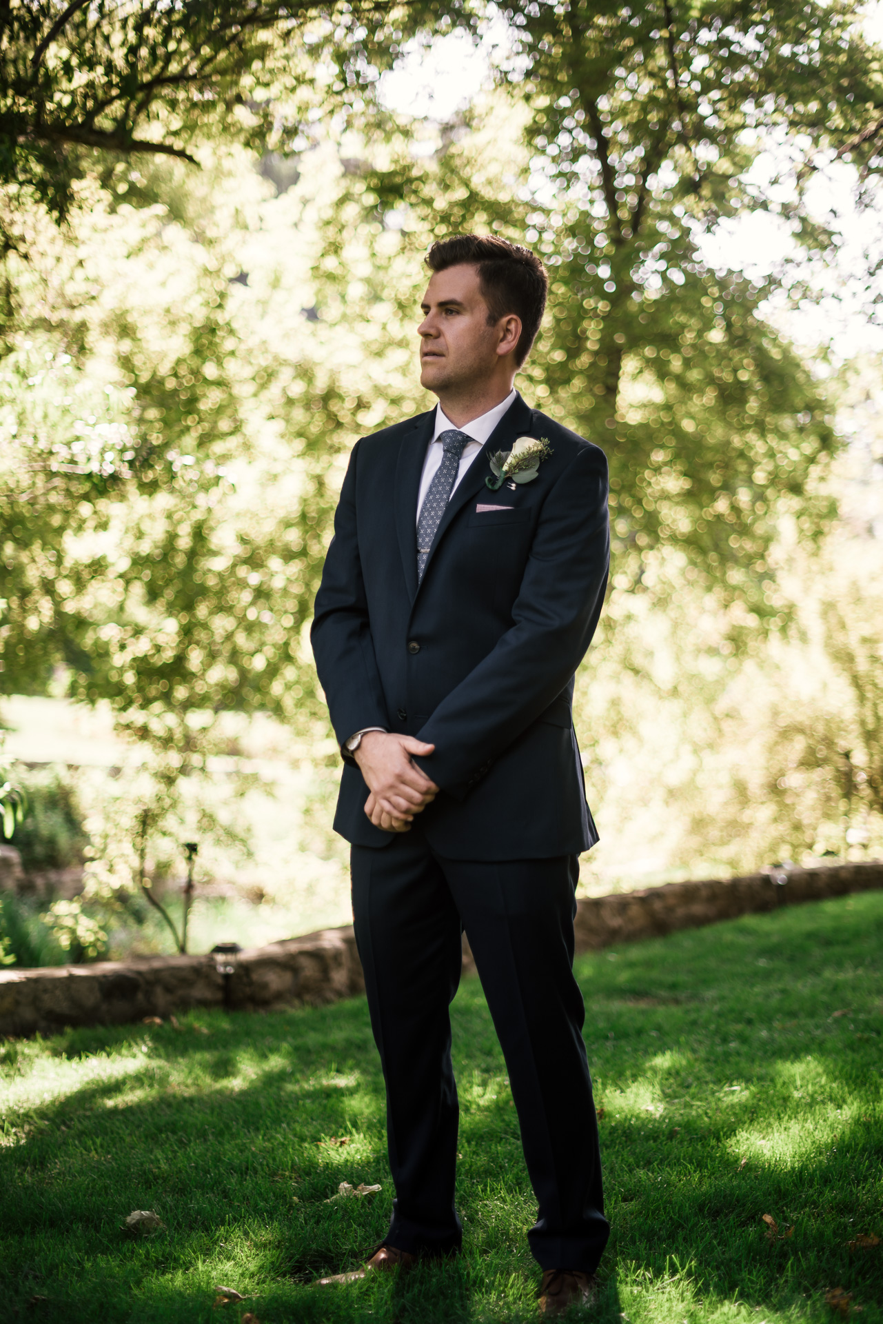 Groom waits for firstlook with his bride at the secret garden located at the Historic Parish ranch in Oak Glen California