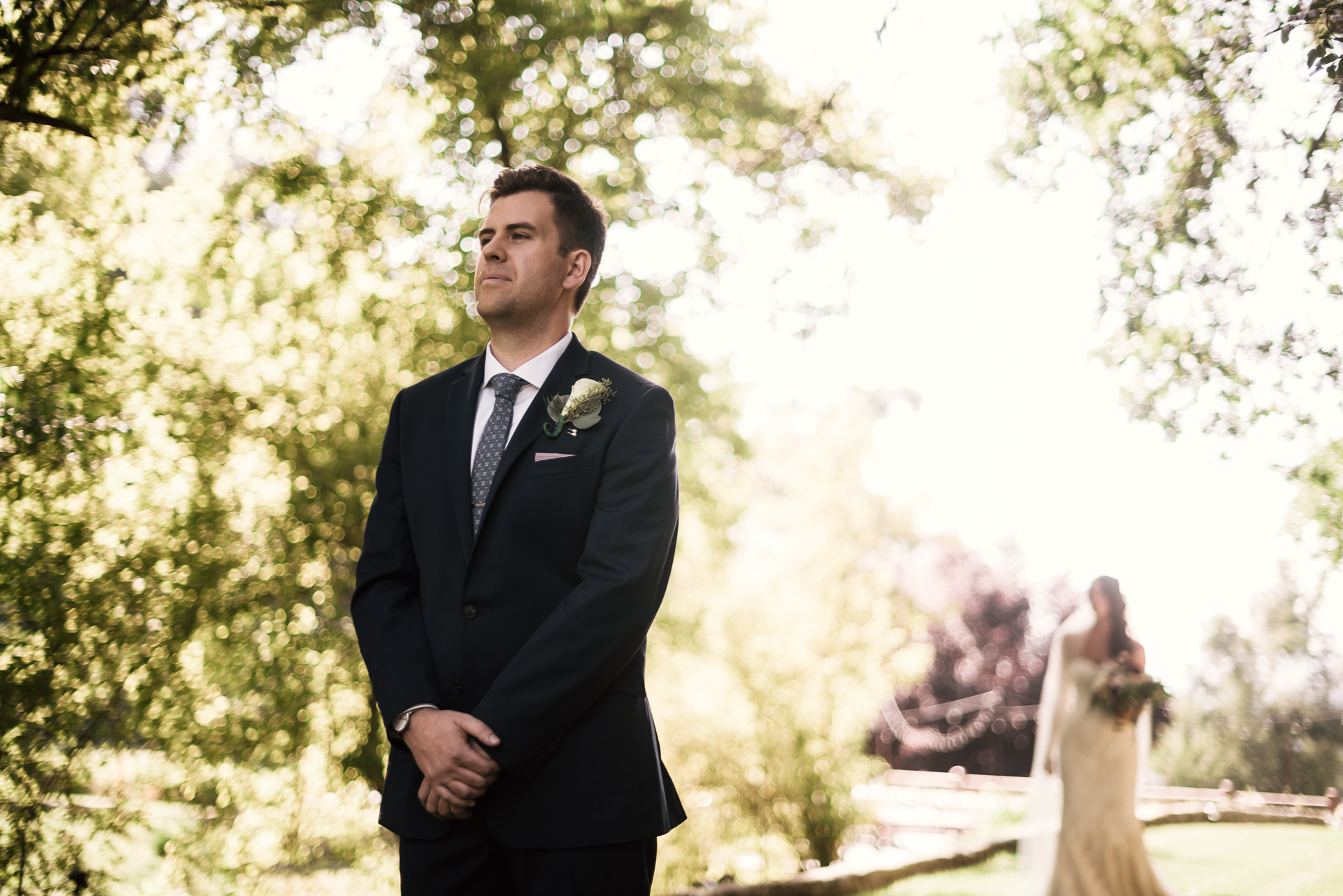groom waits with anticipation as bride approaches for their first look at the secret garden located at the Historic Parish ranch in Oak Glen California