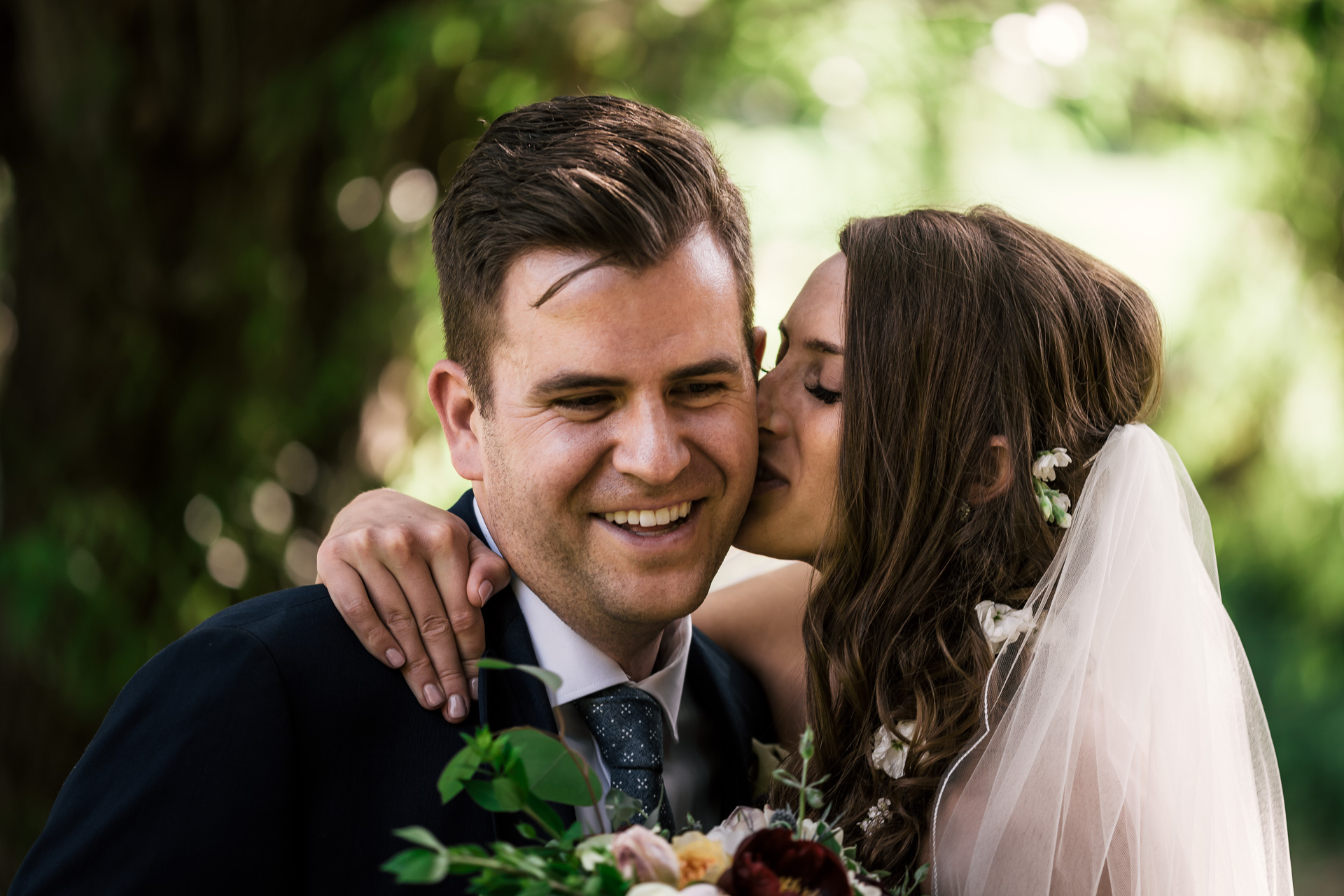 Bride kiss groom on the cheek at the secret garden located at the Historic Parish ranch in Oak Glen California