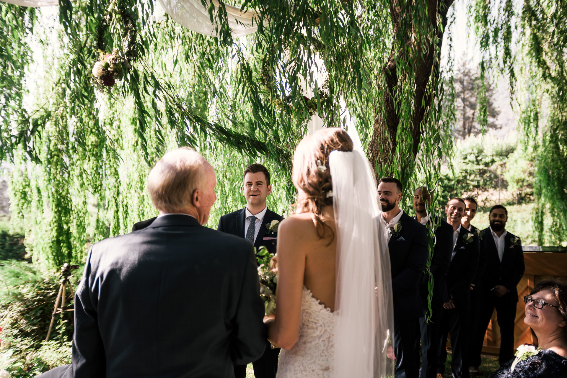 groom sees his bride coming down the aisle at the secret garden located at the Historic Parish ranch in Oak Glen California