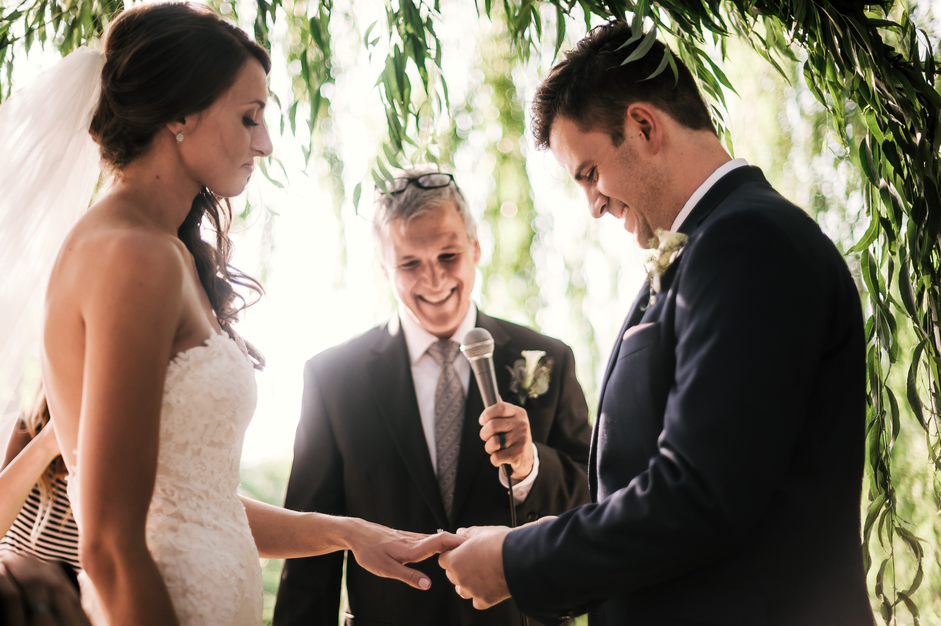 Groom palces ring on brides hand at the secret garden located at the Historic Parish ranch in Oak Glen California