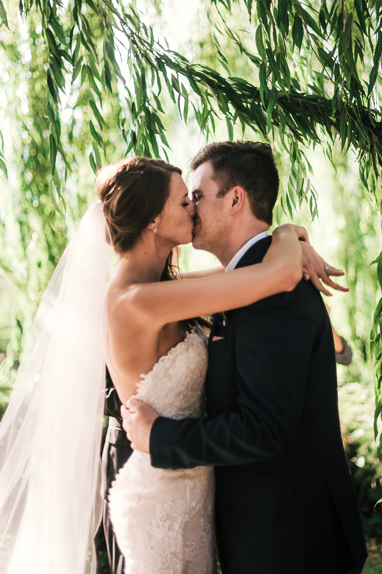 bride and groom share their first kiss as husband and wife at the secret garden located at the Historic Parish ranch in Oak Glen California