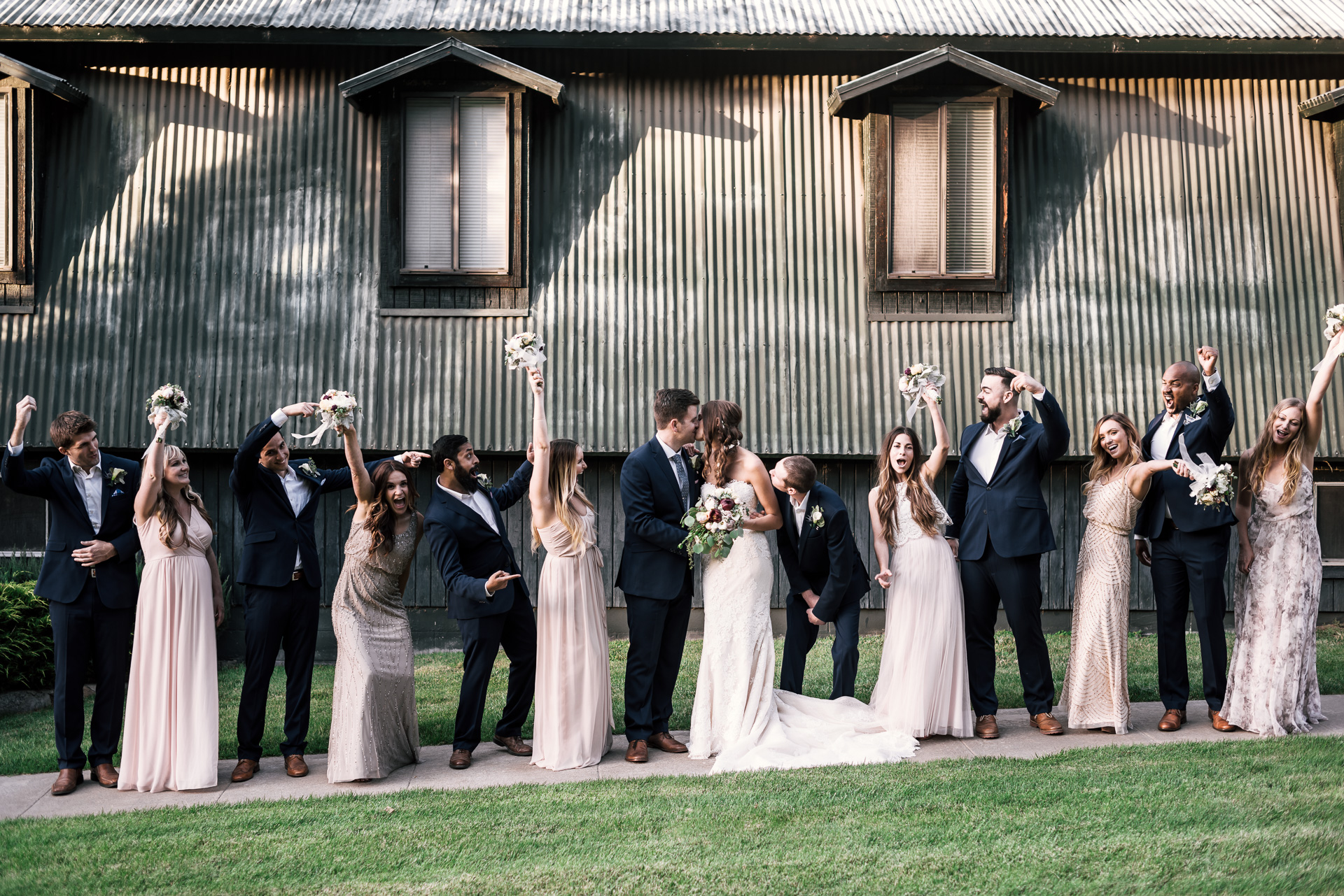 bridal party cheers as the bride and groom kiss at the secret garden located at the Historic Parish ranch in Oak Glen California