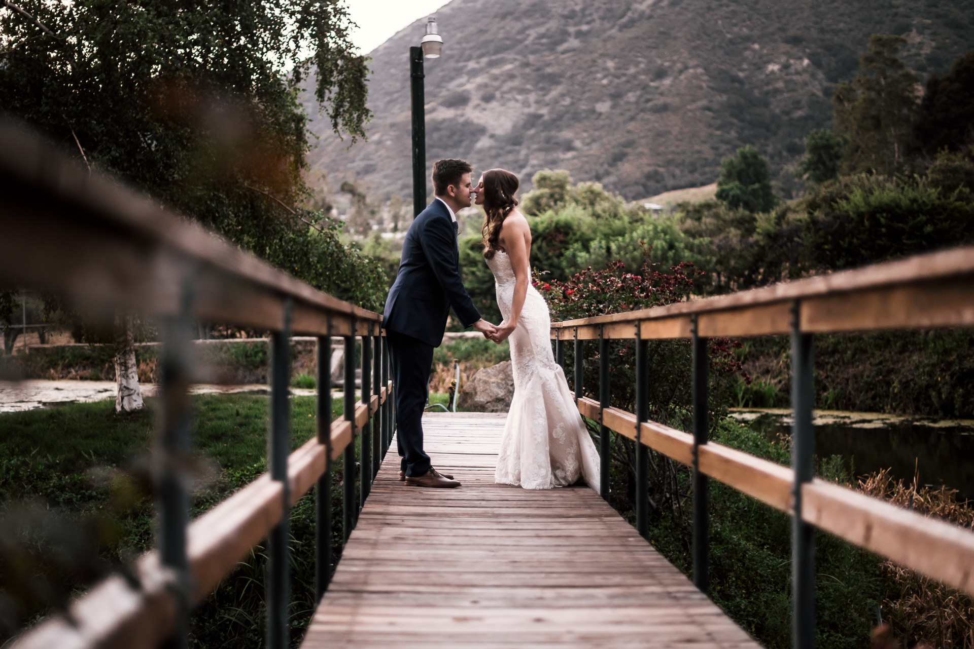 weddign couple kisses on wooden bridge at the secret garden located at the Historic Parish ranch in Oak Glen California