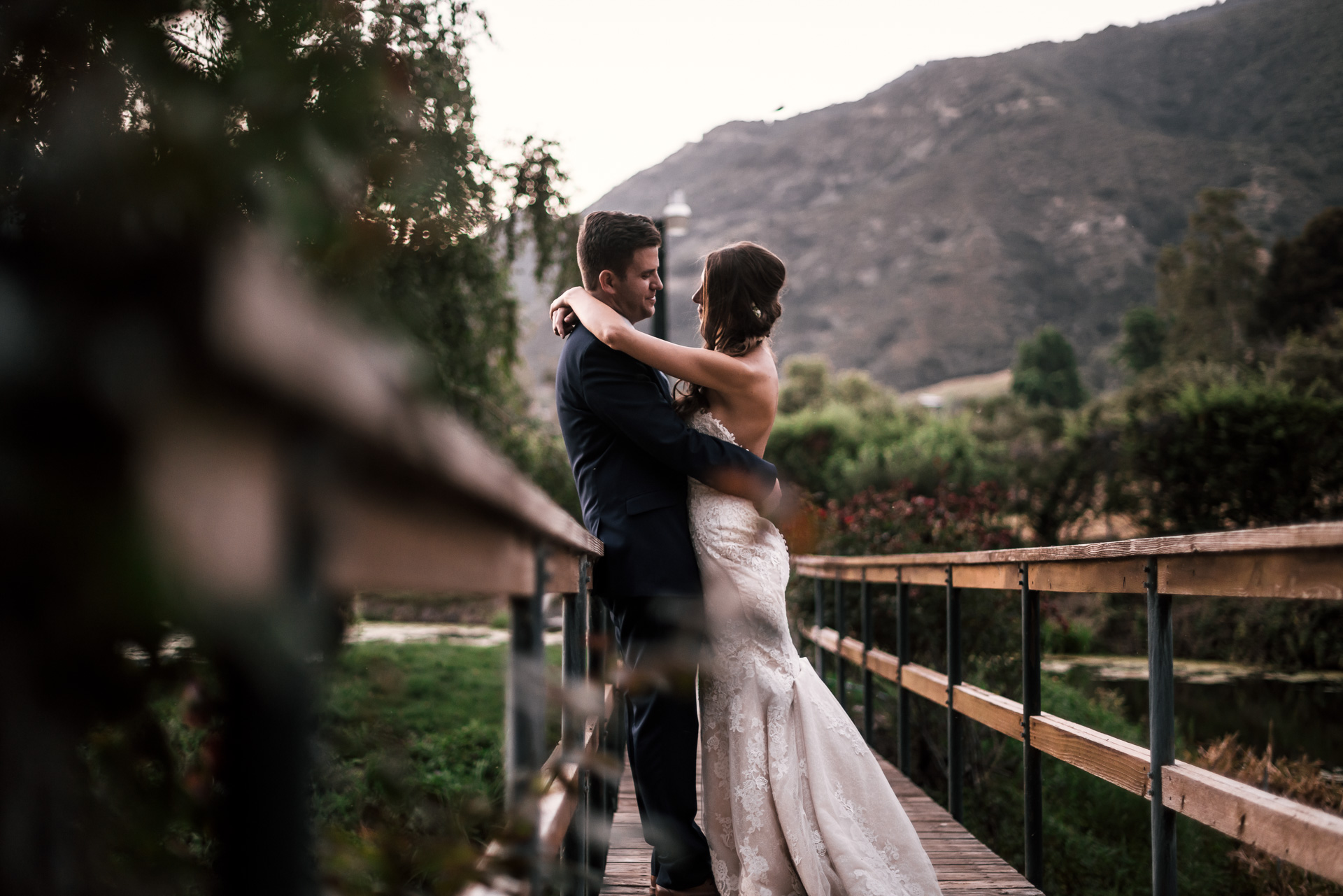 newly weds hold eachother close on rustic bridge at the secret garden located at the Historic Parish ranch in Oak Glen California