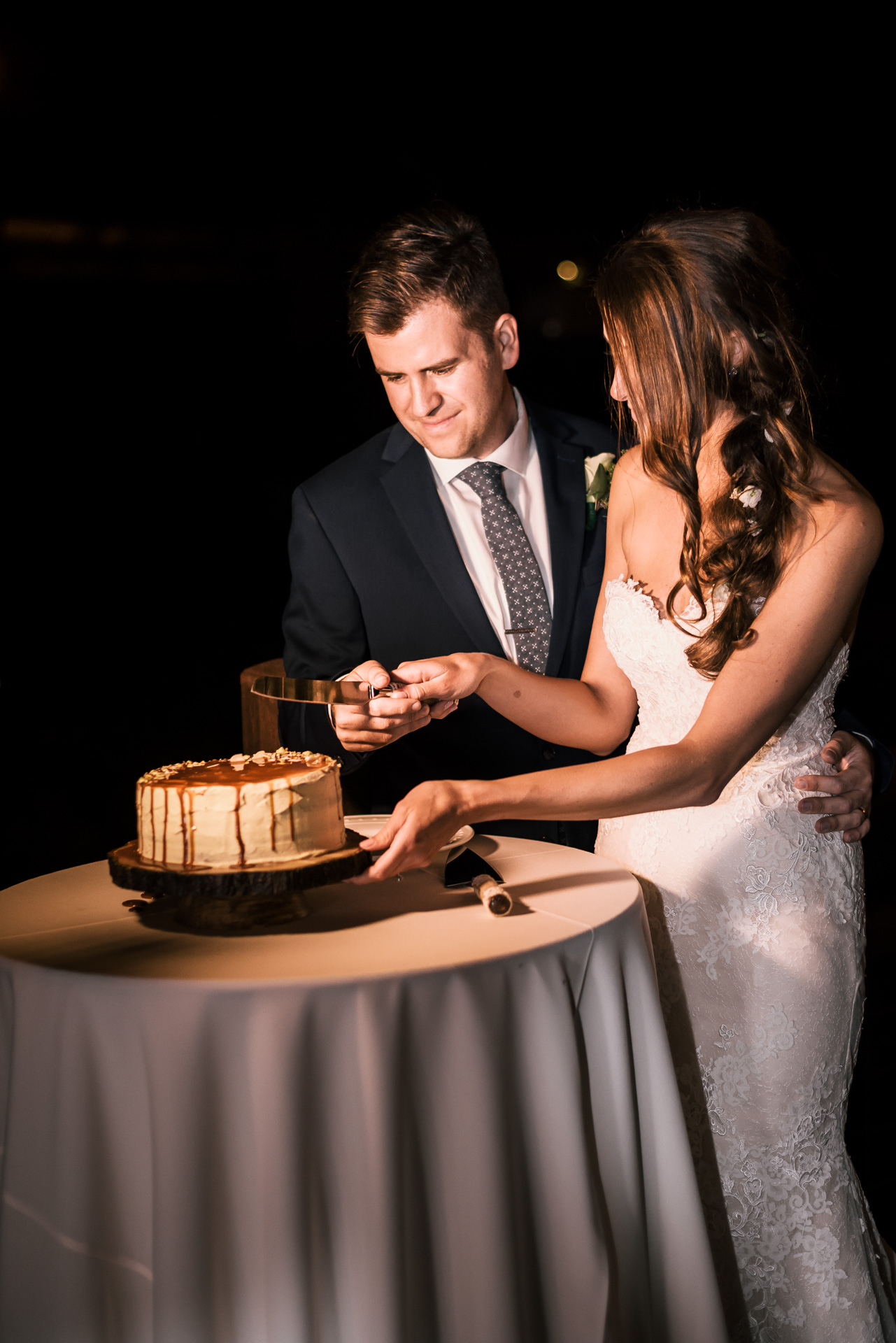 bride and groom cut the wedding cake at the secret garden located at the Historic Parish ranch in Oak Glen California