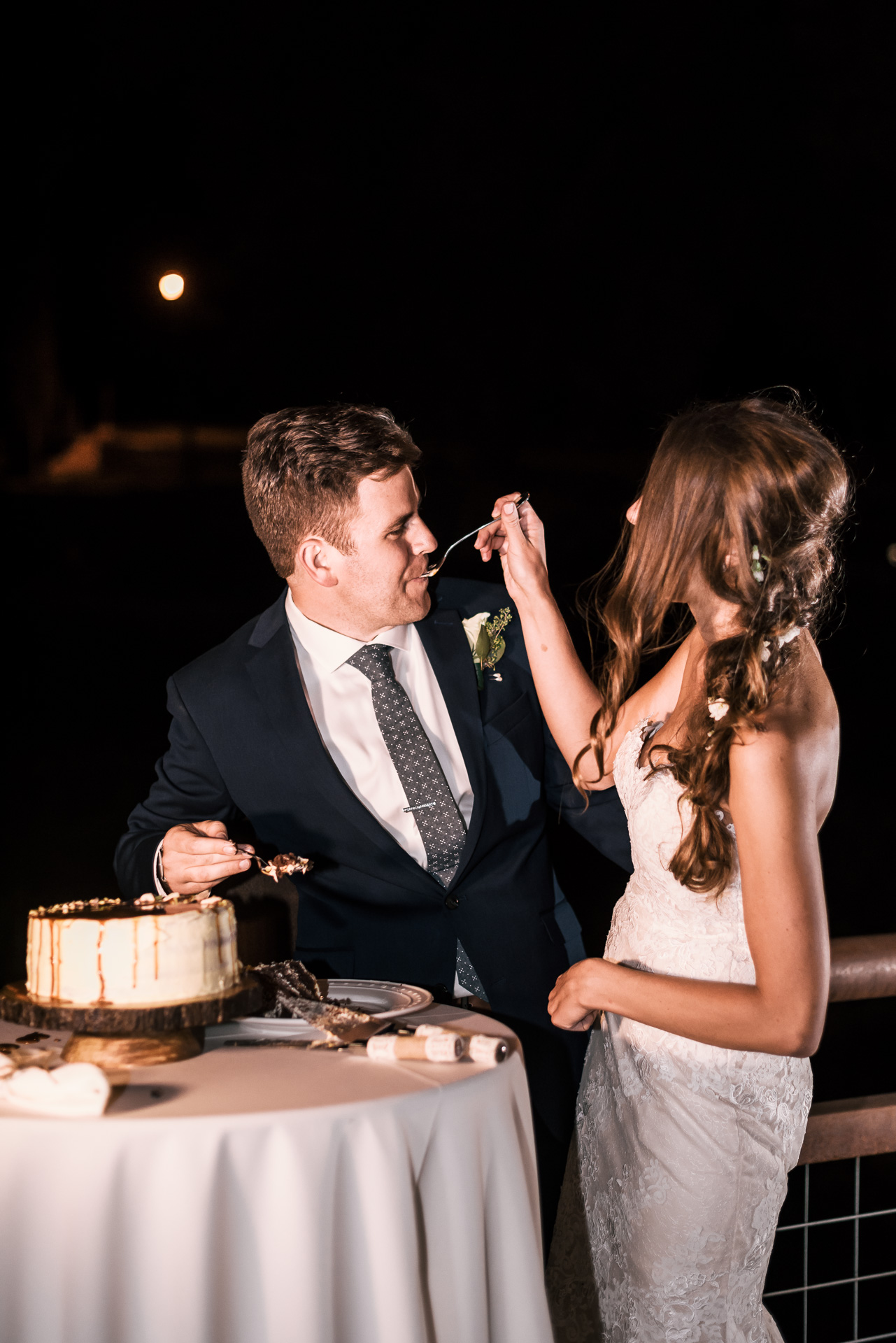 bride feeds groom a piece of cake at the secret garden located at the Historic Parish ranch in Oak Glen California