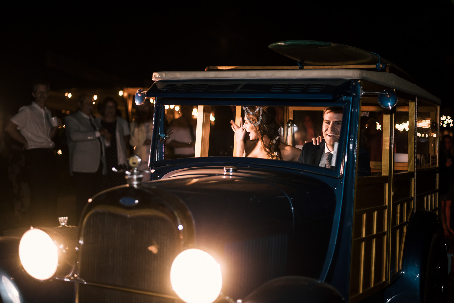 bride and groom make their grand exit in a cool woody car at the secret garden located at the Historic Parish ranch in Oak Glen California