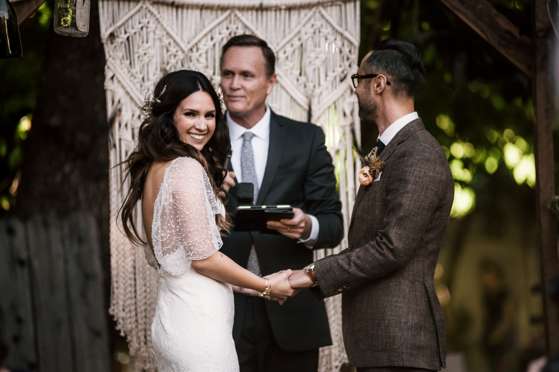 bride looks to her family and friends with a smile shot by wedding photographer at the charming St. George Hotel in Volcano California
