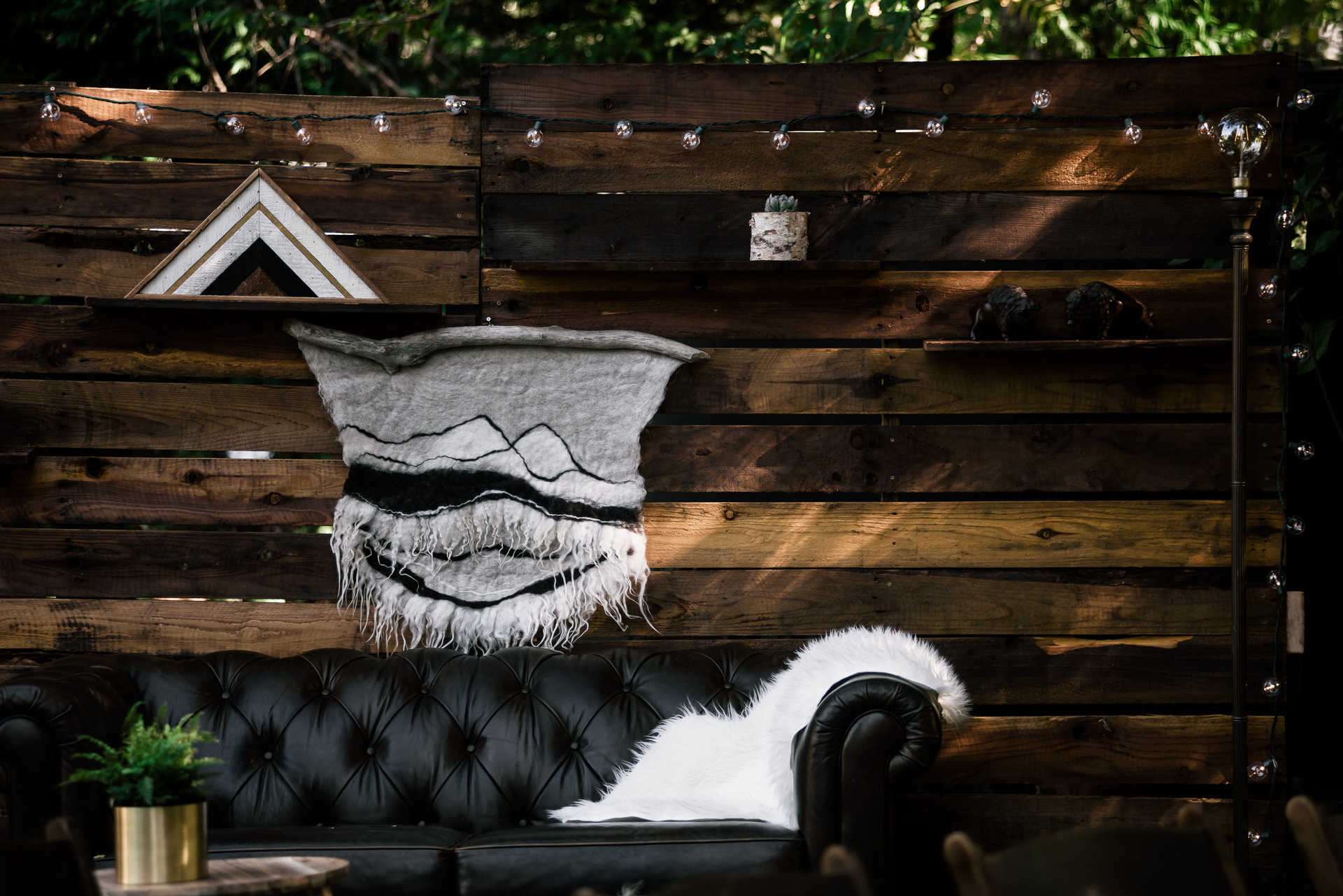leather couch in front of stained wooden pallet wall with shelves and lights shot by wedding photographer at the charming St. George Hotel in Volcano California