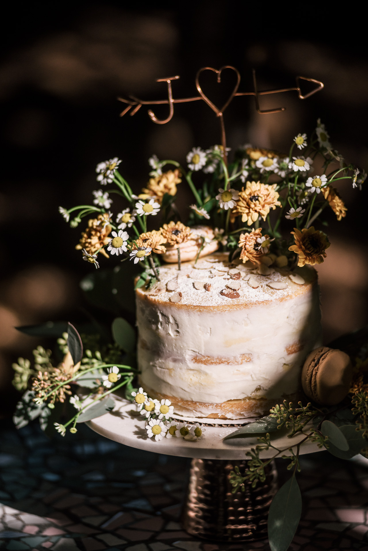adorable wedding cake with daisys and flowers topped with almonds shot by wedding photographer at the charming St. George Hotel in Volcano California