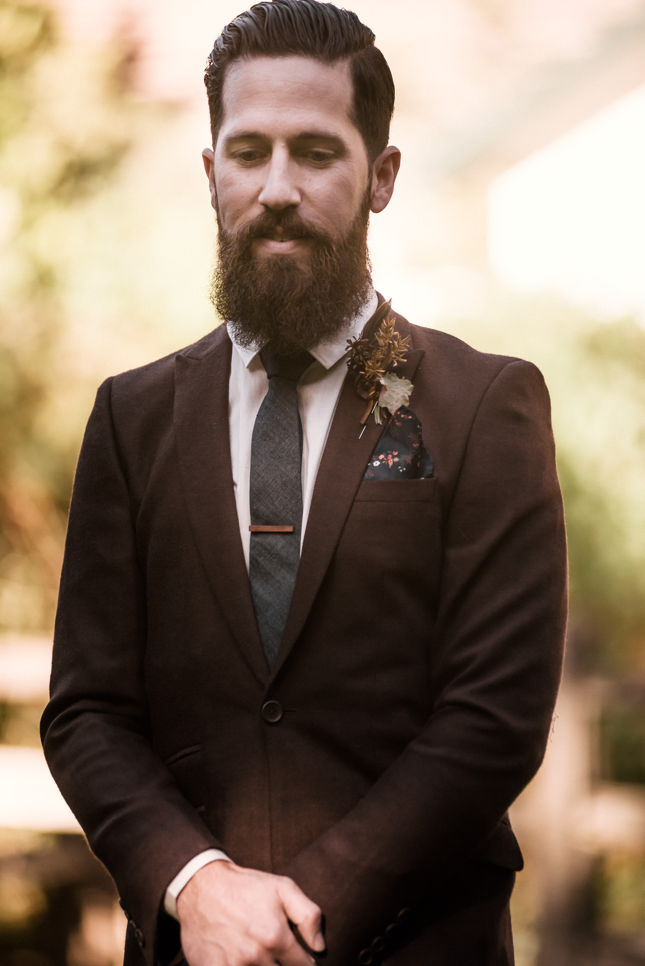 bearded groomsmen in burgandy tux walks down the aisle shot by wedding photographer at the charming St. George Hotel in Volcano California