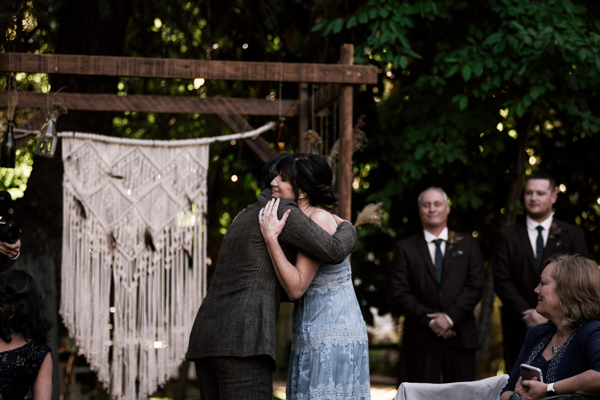 groom hugs his mother in law shot by wedding photographer at the charming St. George Hotel in Volcano California