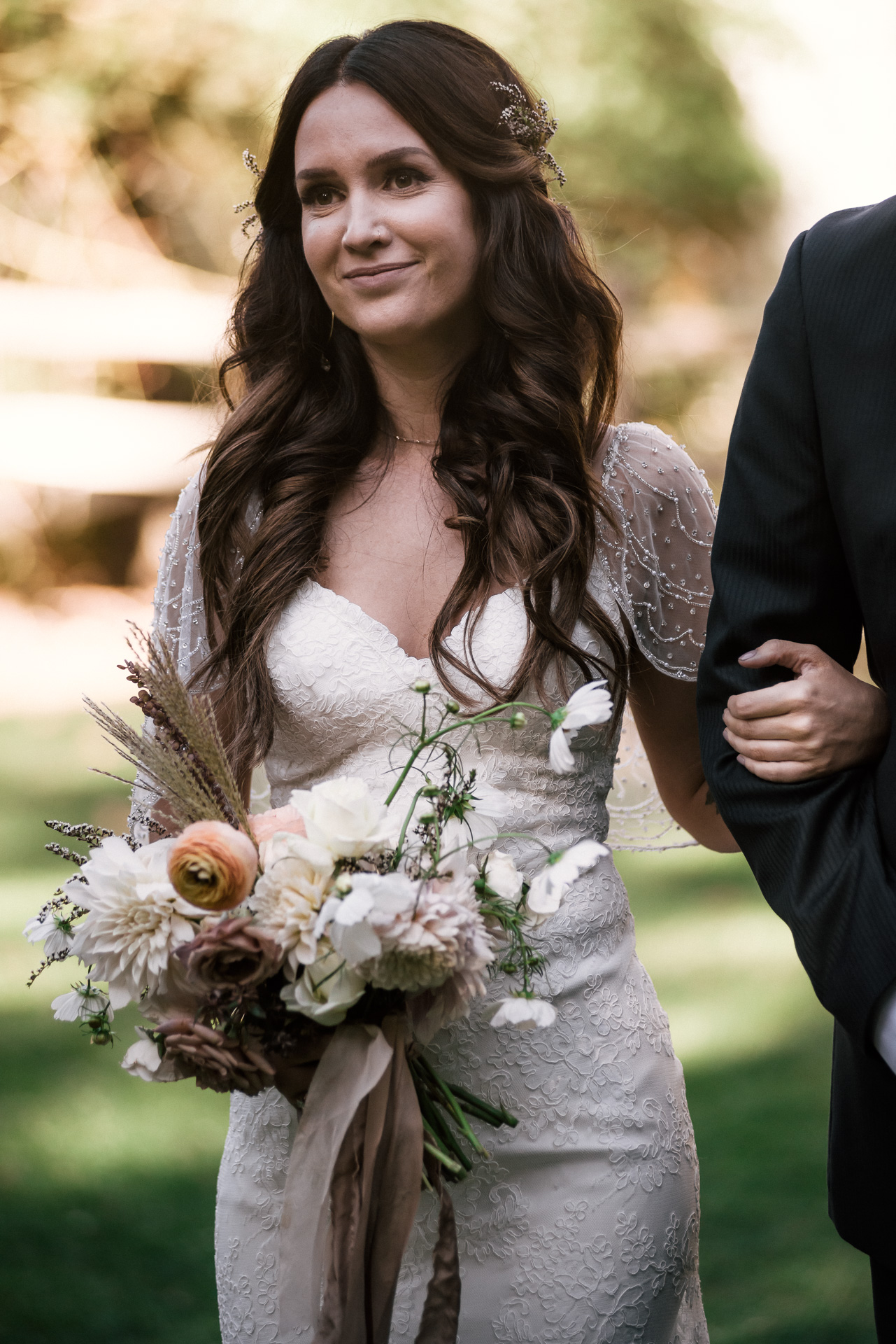 bride wearing lovely wedding dress with lace details and gorgeous vintage bouquet sees her groom for the first time shot by wedding photographer at the charming St. George Hotel in Volcano California