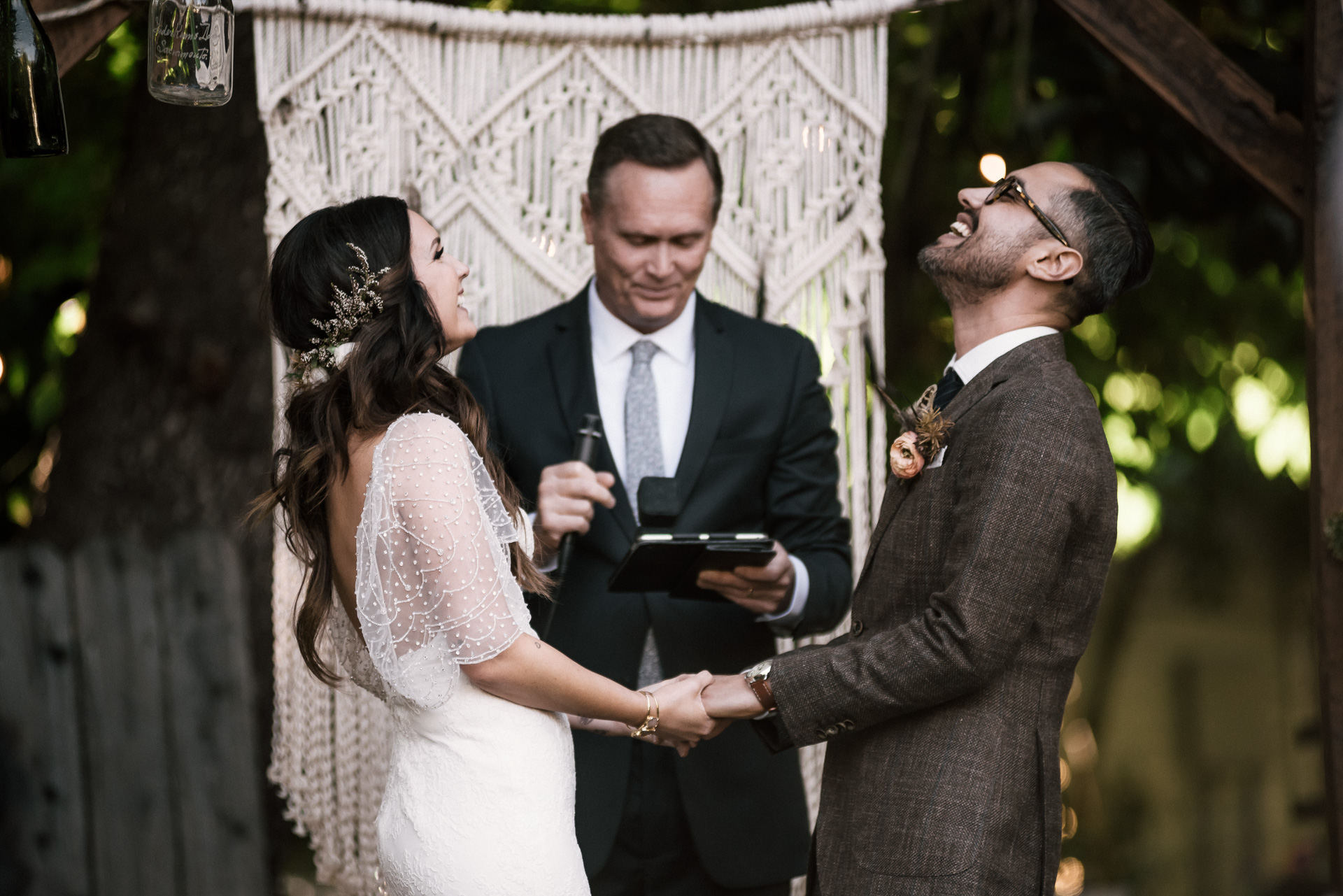 couple shares a big laugh during their ceremony shot by wedding photographer at the charming St. George Hotel in Volcano California