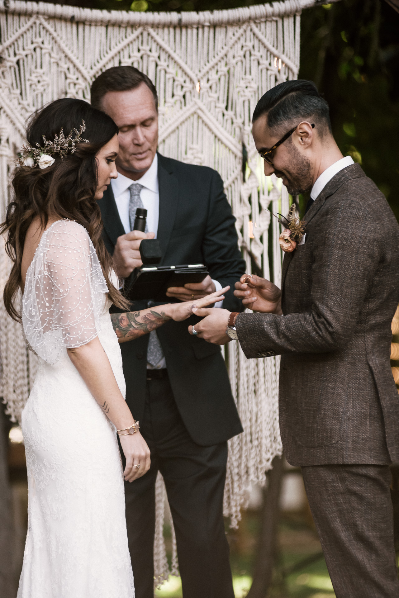 groom places ring on brides finger shot by wedding photographer at the charming St. George Hotel in Volcano California