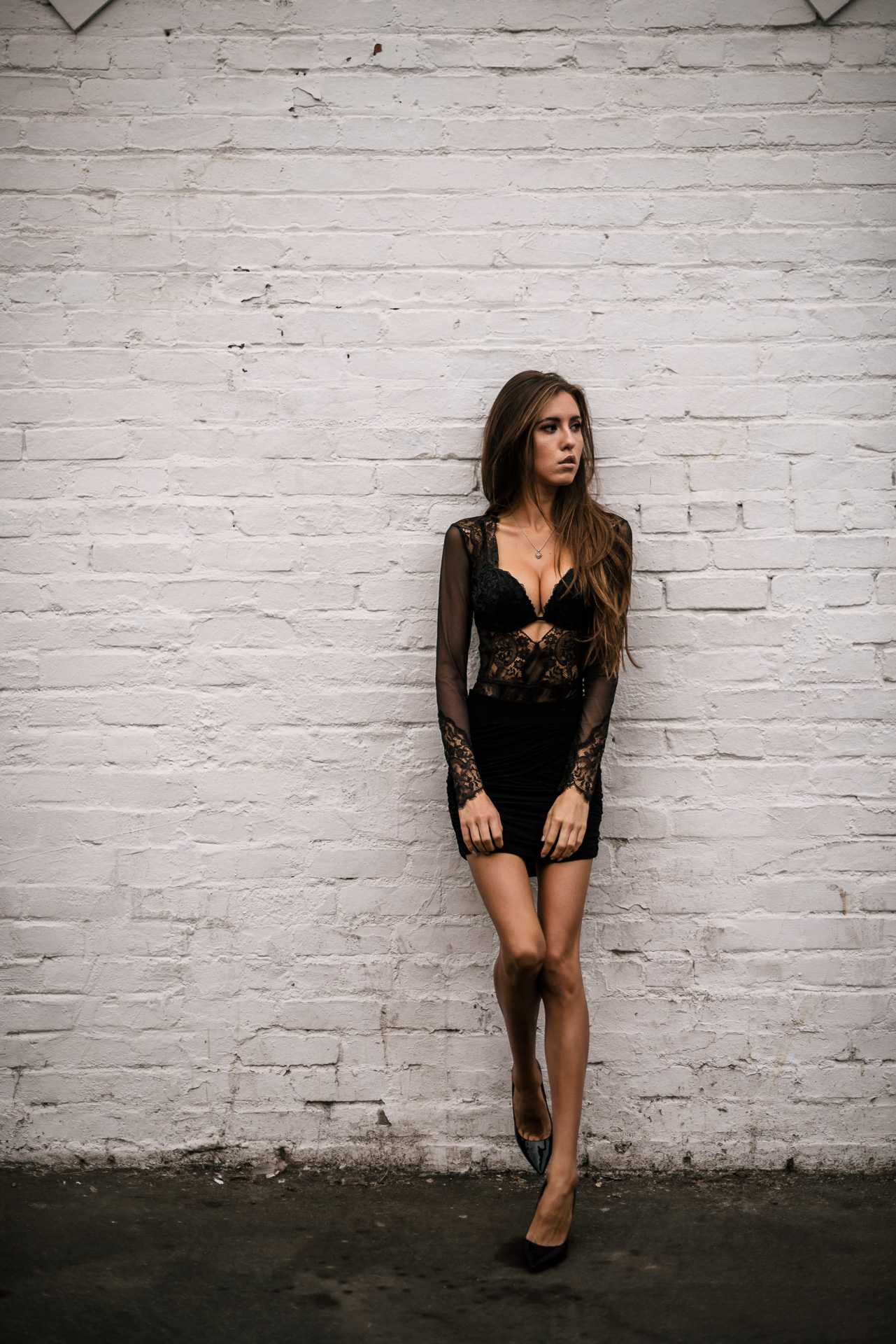 Model leans against white painted brick wall and looks into distance at The Hungarion Brunette Lingerie as outerwear fashion photoshoot in Venice Beach California